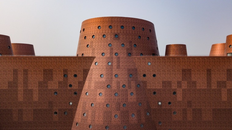 The copper-look facade is actually aluminium cladding.  architecture, castle, fortification, historic site, wall, red