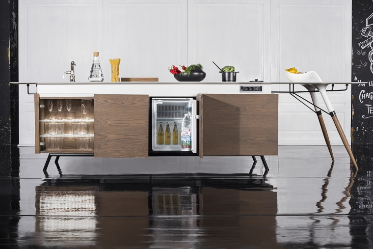 Compact city! The fridge is a large Dometic cabinetry, desk, floor, flooring, furniture, interior design, material property, room, shelf, shelving, sideboard, sofa tables, table, white, black