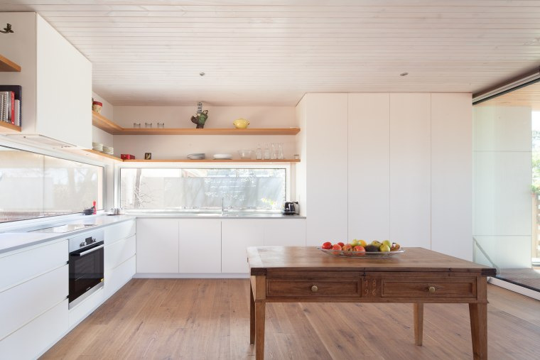 This L-shaped kitchen forms part of a modern building, cabinetry, ceiling, countertop, daylighting, floor, flooring, furniture, hardwood, home, house, interior design, kitchen, laminate flooring, plywood, property, real estate, room, table, wood, wood flooring, gray