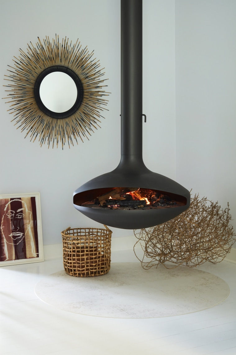 The fireplace hovers above a circular slab of room, gray