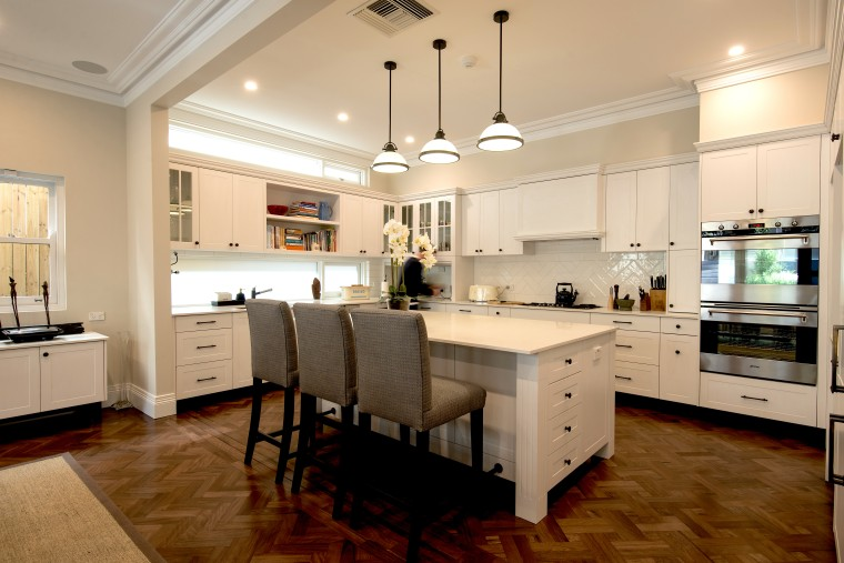 The existing kitchen floors are echoed in the building, cabinetry, ceiling, countertop, cuisine classique, cupboard, design, dining room, floor, flooring, furniture, hardwood, home, house, interior design, kitchen, laminate flooring, light fixture, lighting, major appliance, property, real estate, refrigerator, room, sink, table, wood, wood flooring, orange