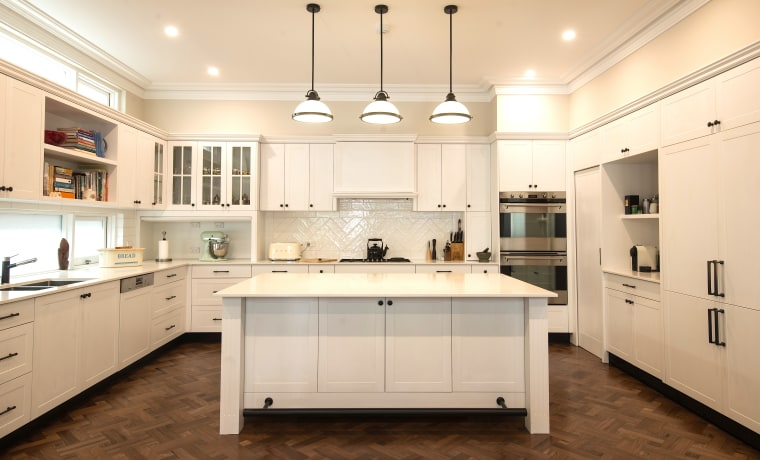 Classic cream cabinetry complements the parquet flooring in building, cabinetry, ceiling, countertop, cuisine classique, cupboard, floor, flooring, furniture, hardwood, home, house, interior design, kitchen, light fixture, lighting, material property, property, real estate, room, sink, tile, wood flooring, orange