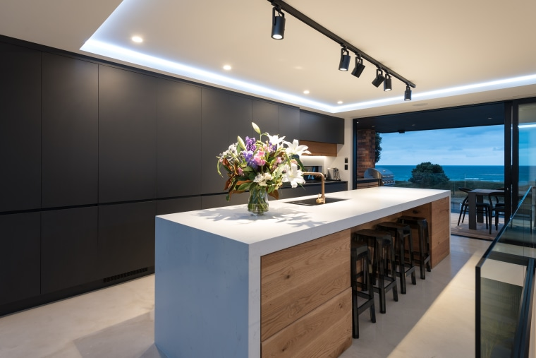 ​​​​​​​A white waterfall benchtop flowing over a wood-fronted architecture, countertop, interior design, kitchen, waterfall benchtop,  timber, black cabinetry