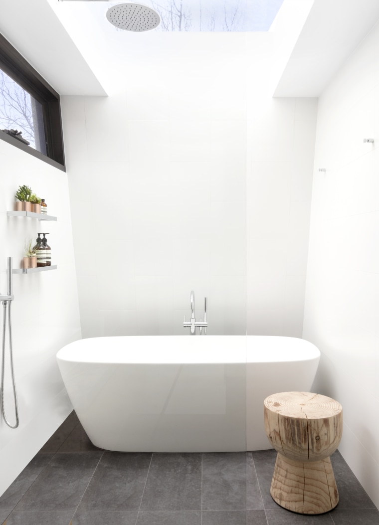 ​​​​​​​A large skylight over the shower, a soft-edged architecture, bathroom, bathtub, ceramic tiles, floor, flooring, plumbing fixtures, tap, tile, rainhead shower