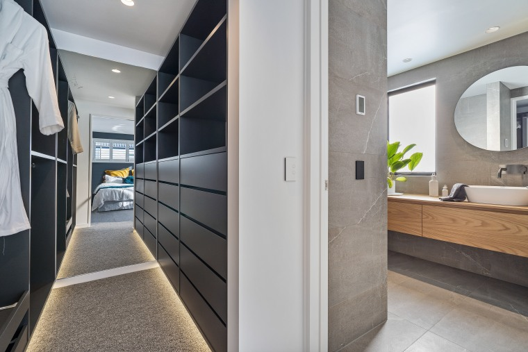 A long walk-through dressing area connects the master architecture, building, ceiling, door, floor, flooring, furniture, glass, house, interior design, property, real estate, room, wall, gray