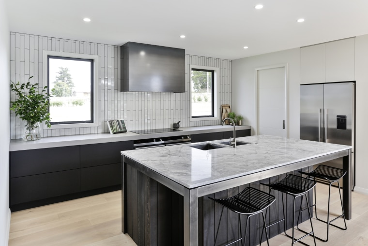 ​​​​​​​A slender granite island benchtop contrasts with a building, cabinetry, ceiling, countertop, floor, furniture, home, house, interior design, kitchen, material property, property, real estate, room, table, tile, gray