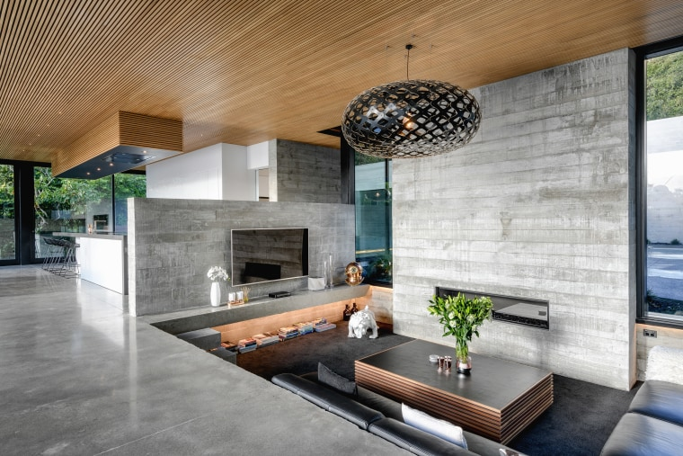 The home's tilt slab concrete walls have a architecture, building, ceiling, concrete, design, floor, flooring, furniture, home, house, interior design, living room, lobby, property, real estate, room, table, tile, wall, gray
