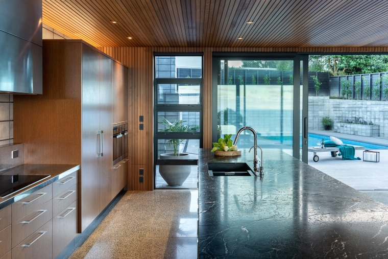 Open to the surrounding spaces, this kitchen is apartment, architecture, building, ceiling, countertop, daylighting, estate, floor, flooring, furniture, glass, hardwood, home, house, interior design, kitchen, property, real estate, residential area, room, window, wood
