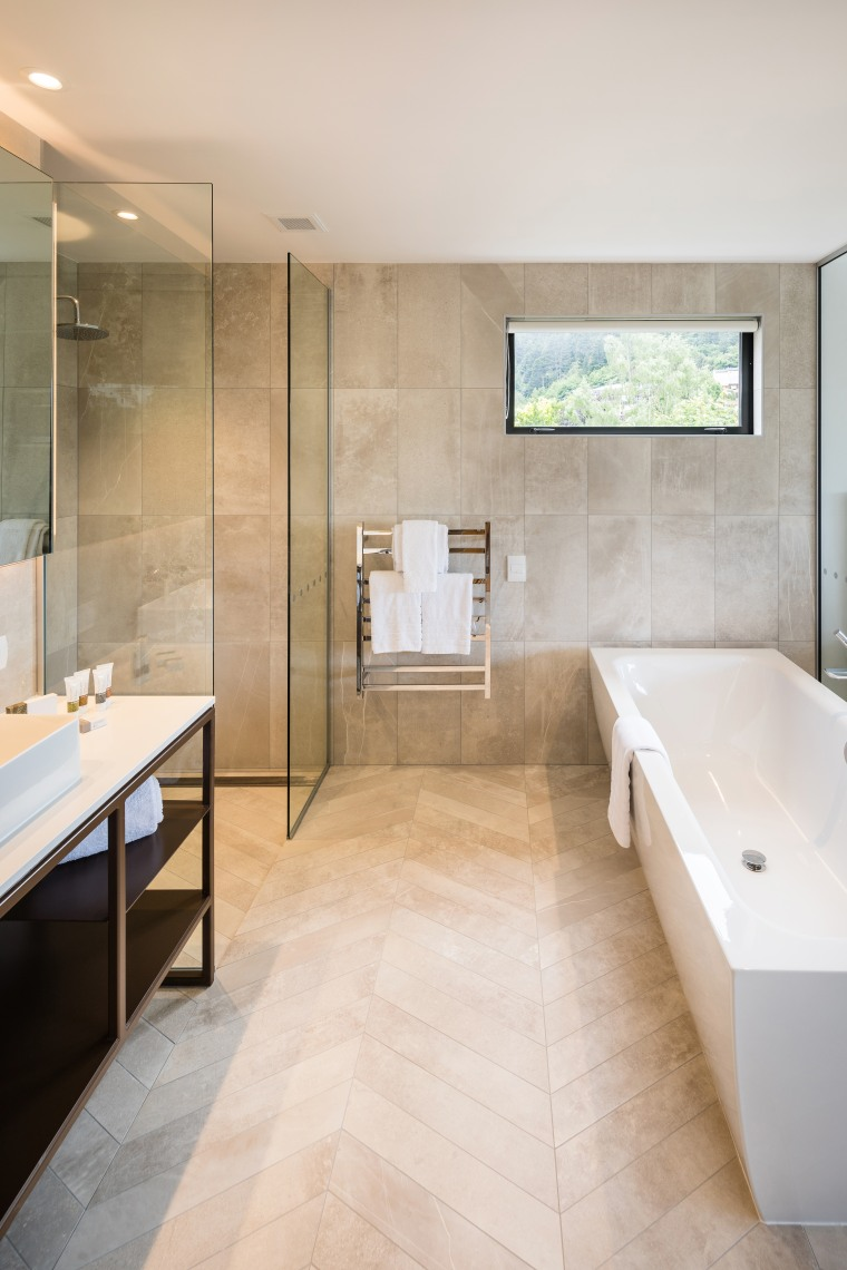 Clean-lined and contemporary, this custom steel-framed vanity is architecture, bathroom, bathtub, beige, building, ceiling, floor, flooring, furniture, home, house, interior design, plumbing fixture, property, real estate, room, sink, tile, wall, gray