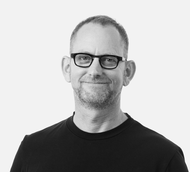 Chris Paterson, senior principal at Populous beard, black, black-and-white, cool, eyewear, facial hair, gentleman, glasses, male, monochrome, monochrome photography, neck, photograph, photography, portrait, sleeve, standing, stock photography, t-shirt, vision care, white, white, black