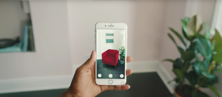 Ikea's Place app uses augmented reality communication device, electronic device, feature phone, finger, gadget, hand, iphone, mobile phone, photography, plant, portable communications device, red, smartphone, technology, telephone, gray