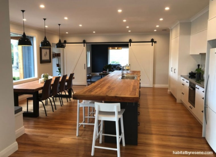 The interior of this Gisborne farmhouse is predominately building, cabinetry, ceiling, countertop, dining room, floor, flooring, furniture, hardwood, home, house, interior design, kitchen, laminate flooring, light fixture, lighting, property, real estate, room, table, wood, wood flooring, brown
