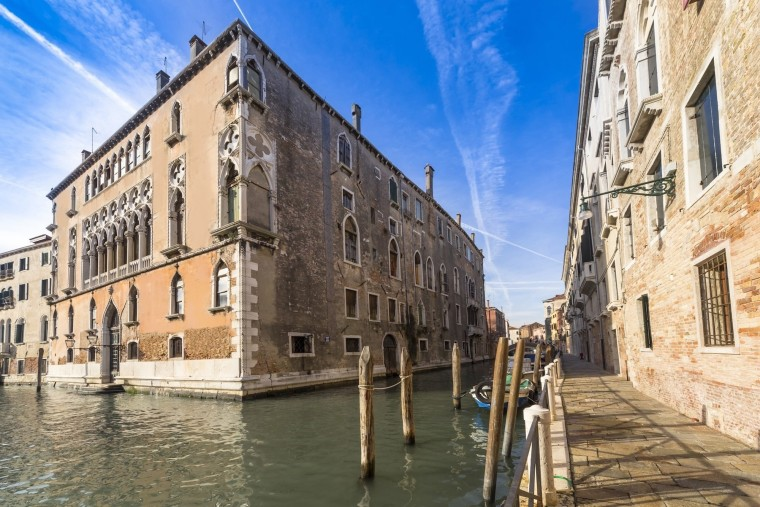 Located in the centre of the city, the building, canal, city, facade, historic site, medieval architecture, sky, tourist attraction, town, waterway, orange