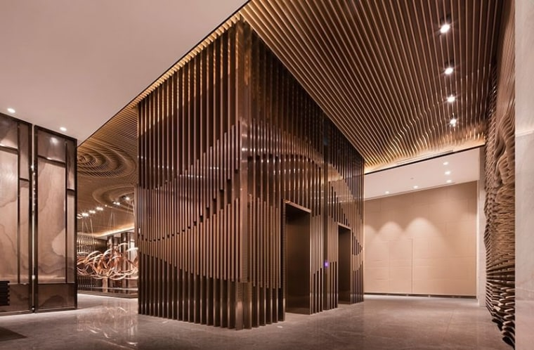 Slats run around this elevator and along the architecture, ceiling, facade, interior design, lobby, brown, orange
