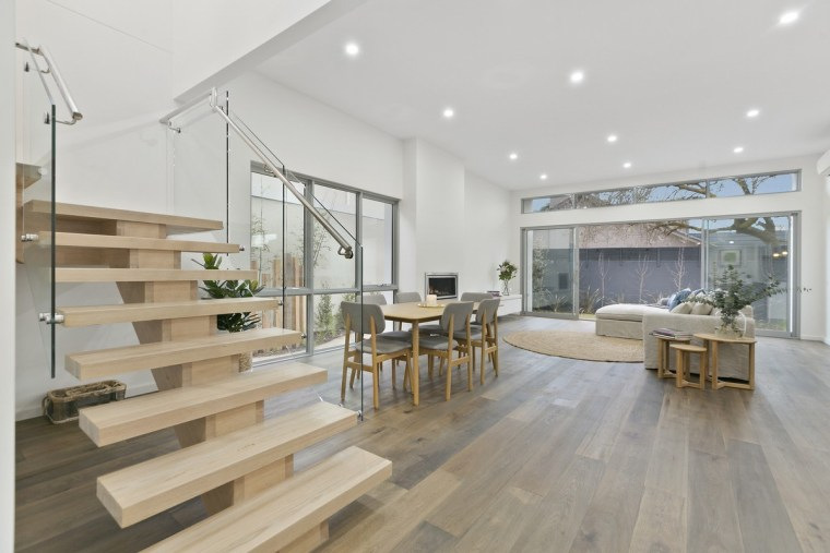 The glass balustrade sandwiches these floating wood steps floor, flooring, house, interior design, laminate flooring, living room, real estate, wood, wood flooring, gray