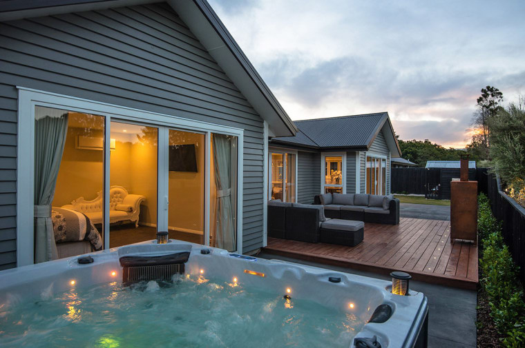 Spa area and evening light on NZ weatherboard backyard, cottage, estate, home, house, outdoor structure, property, real estate, siding, swimming pool, window, black