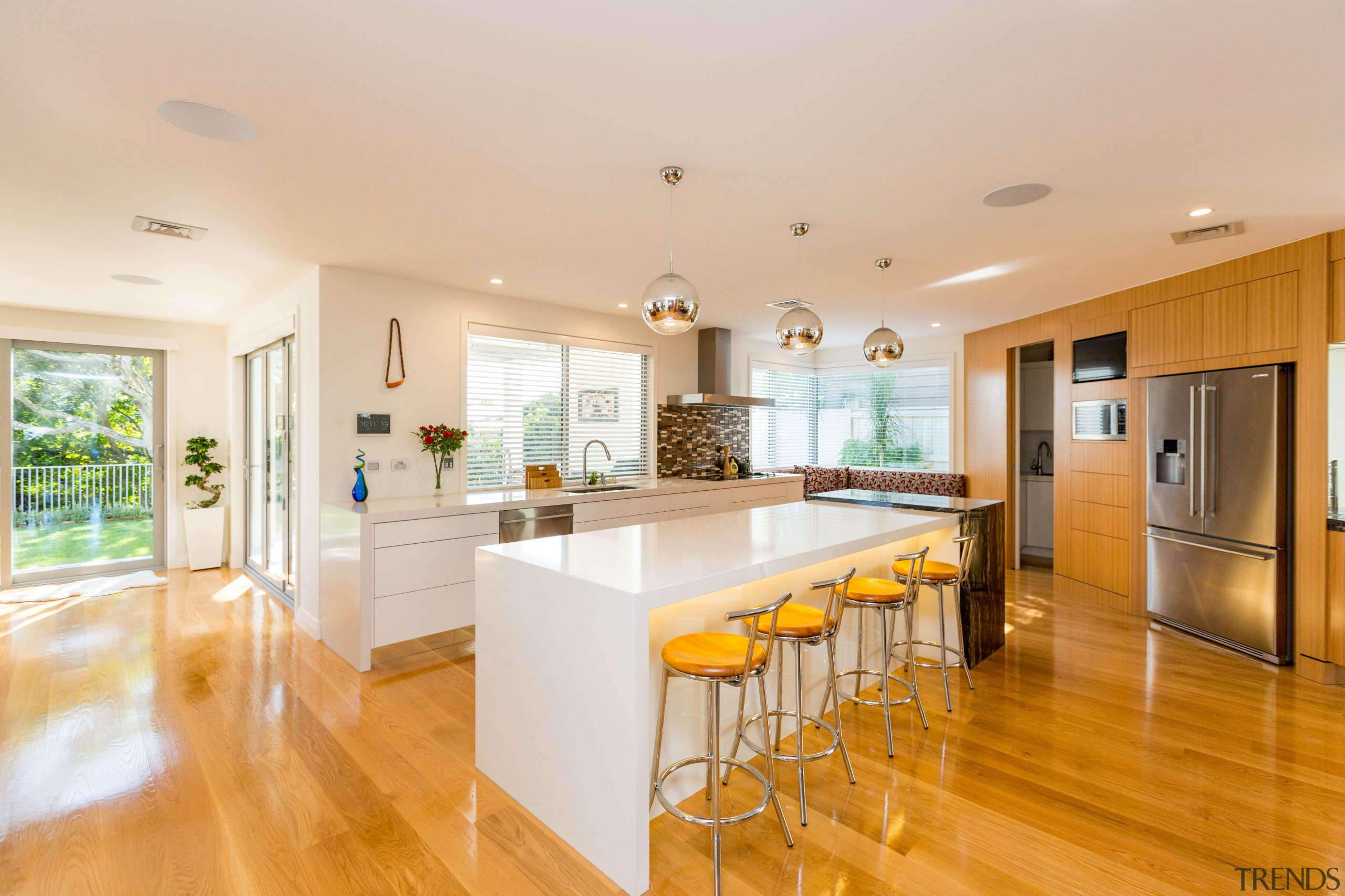 An expansive, light-filled kitchen is the hub of ceiling, countertop, estate, floor, flooring, hardwood, home, interior design, kitchen, laminate flooring, real estate, room, wood flooring, white, orange
