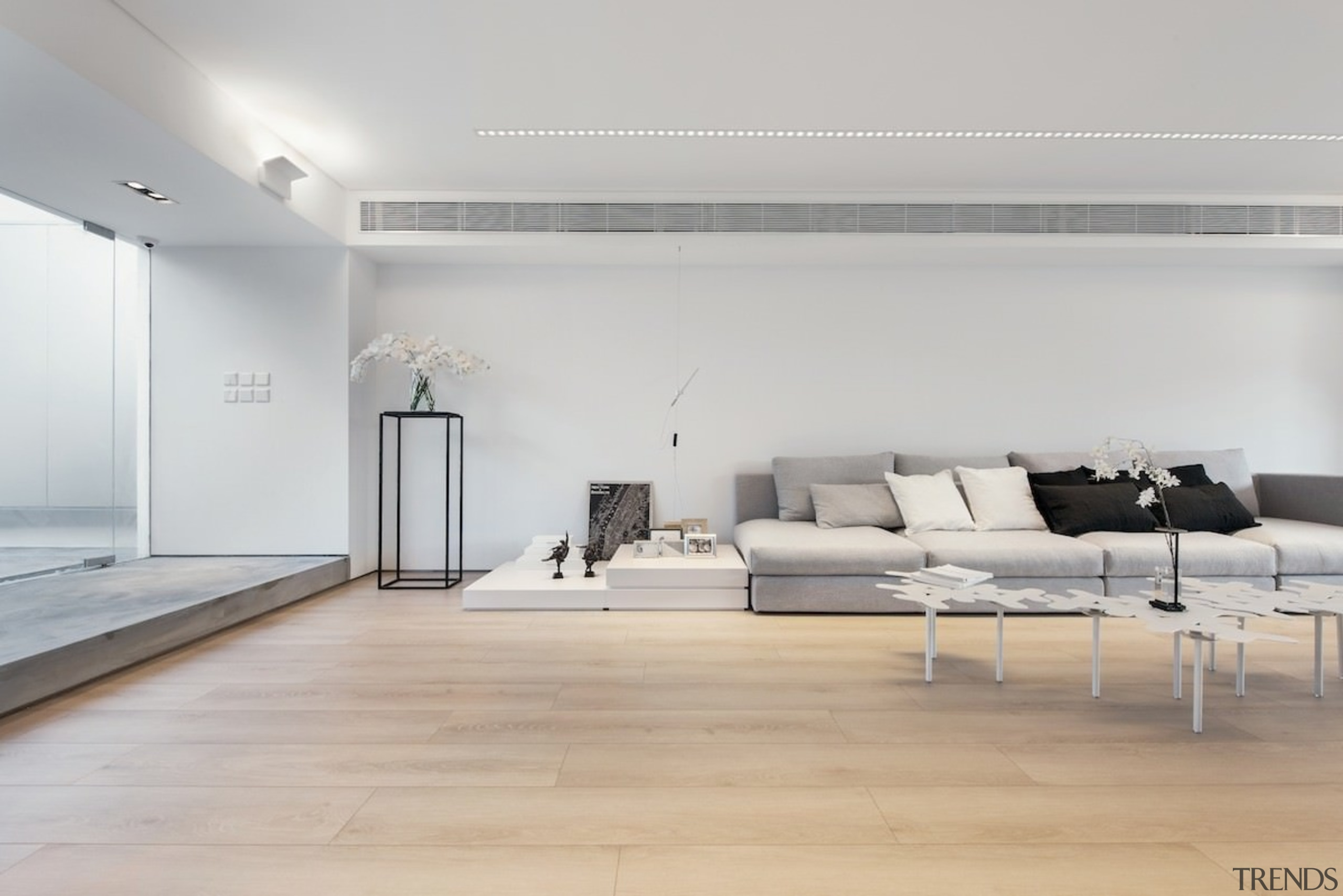 This expansive living room has the feel of architecture, ceiling, floor, flooring, furniture, interior design, laminate flooring, living room, product design, table, wall, wood, wood flooring, gray
