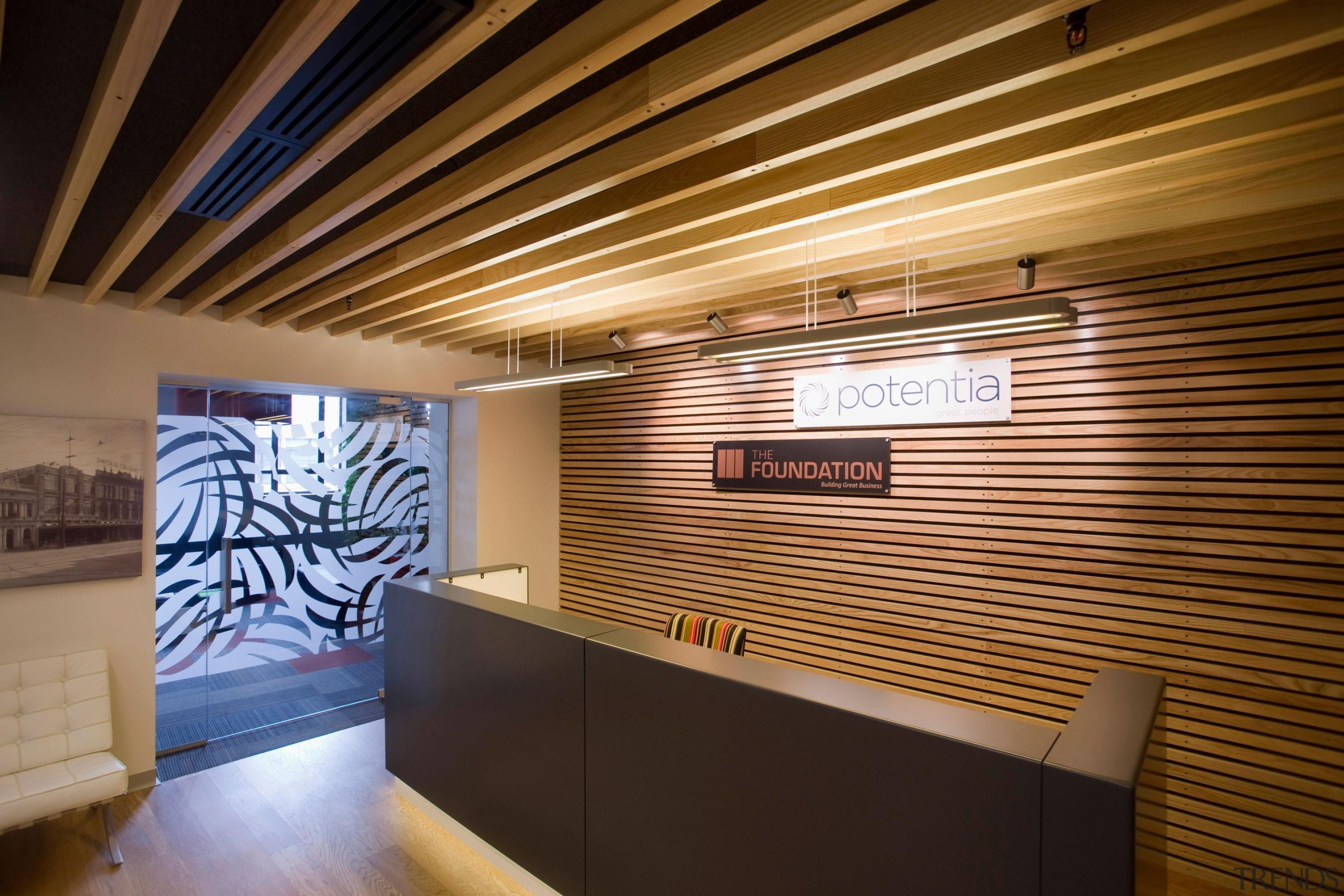 A steel-clad reception counter sits within the warmth architecture, ceiling, interior design, lobby, wall, brown