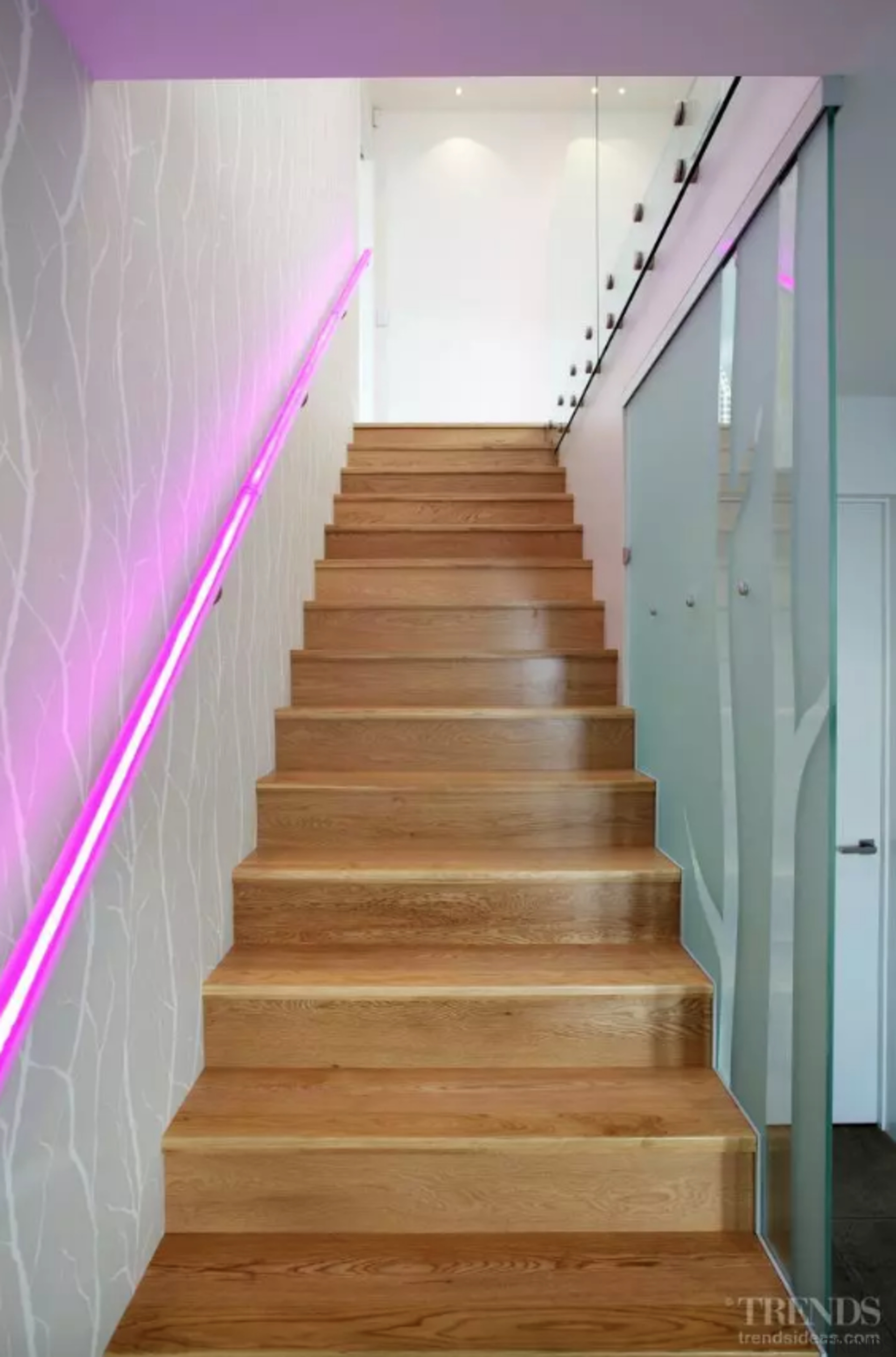 Etched glass and colour-changing LED lights decorate the architecture, baluster, building, ceiling, floor, flooring, handrail, hardwood, home, house, interior design, laminate flooring, property, real estate, room, stairs, wood, wood flooring, gray, brown