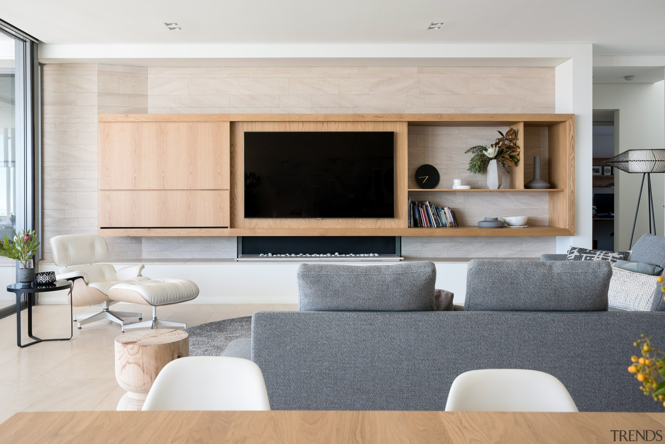 Custom built-in cabinetry accommodates the television in this building, cabinetry, ceiling, coffee table, couch, design, fireplace, floor, flooring, furniture, hardwood, home, house, interior design, living room, property, real estate, room, table, wall, wood flooring, gray