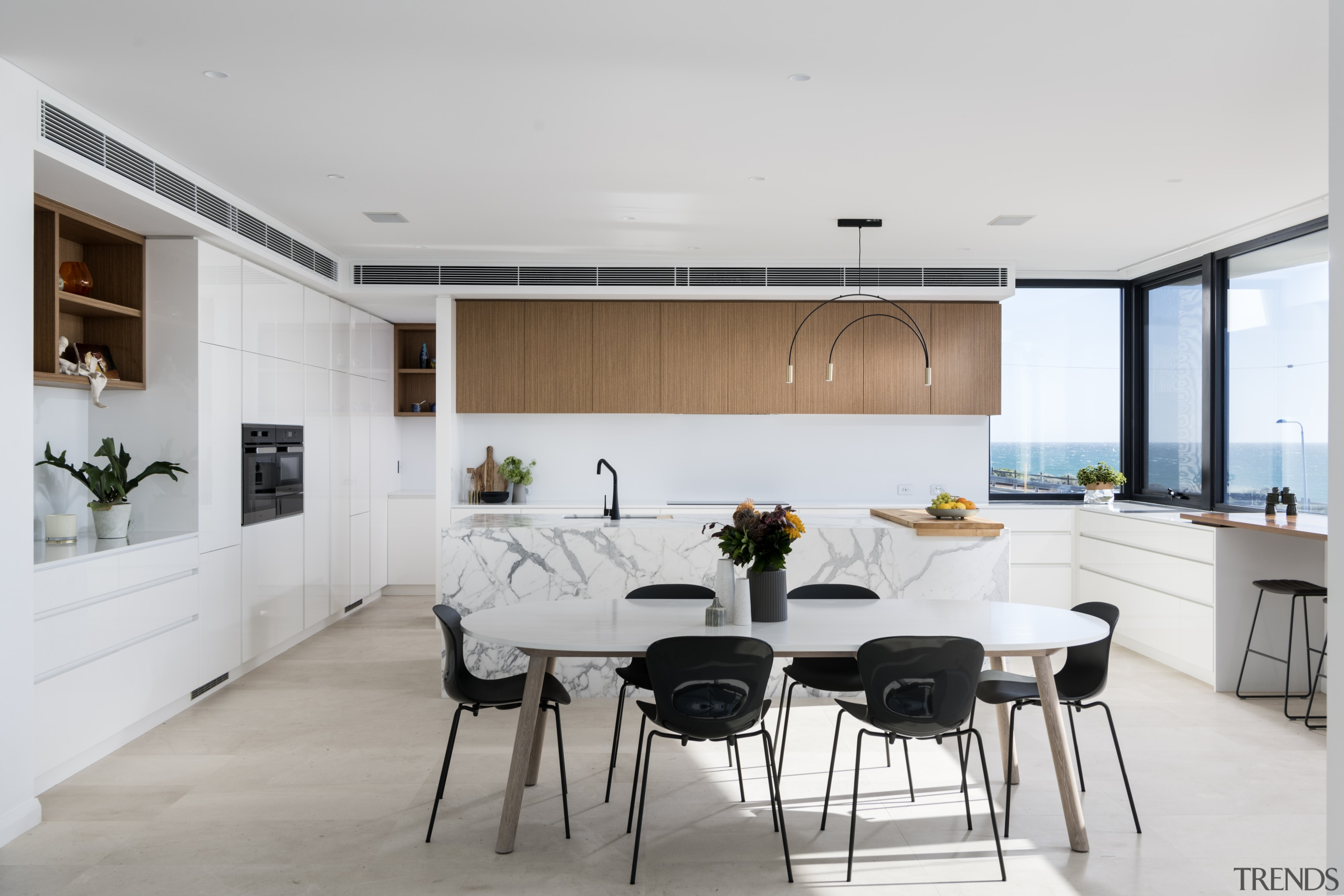 A long marble-clad kitchen island is the central architecture, bar stool, cabinetry, chairs, countertop, dining room, floor, flooring, furniture, home, house, interior design, kitchen, room, table, gray, white, chopping board