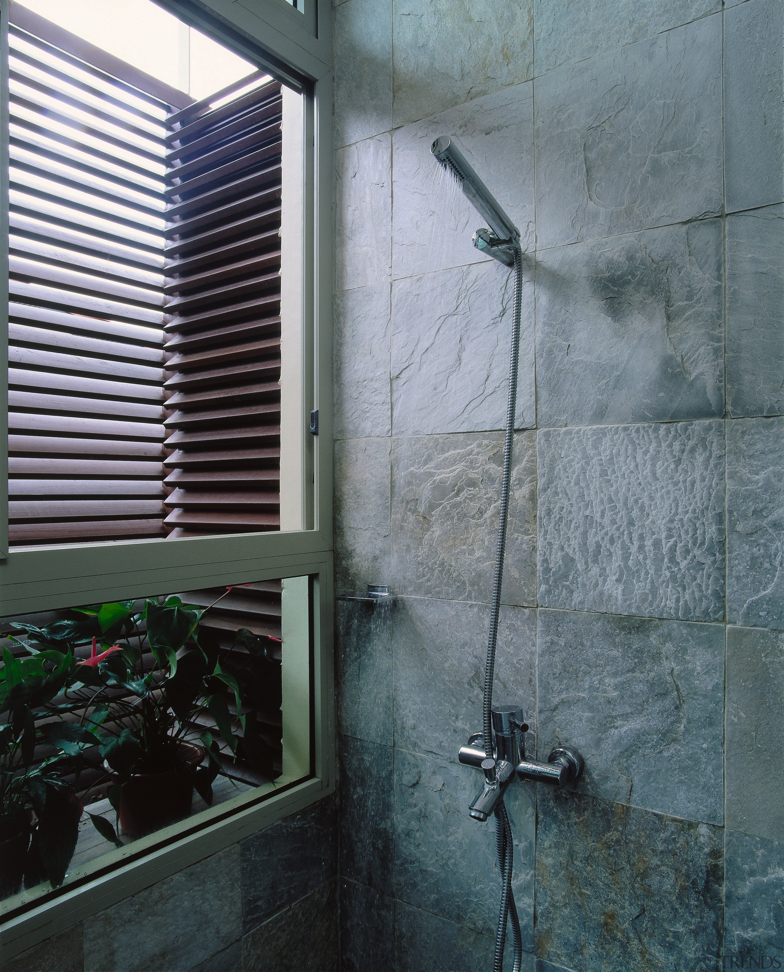 The detail of a shower with stone wall architecture, glass, house, plumbing fixture, wall, window, gray, black