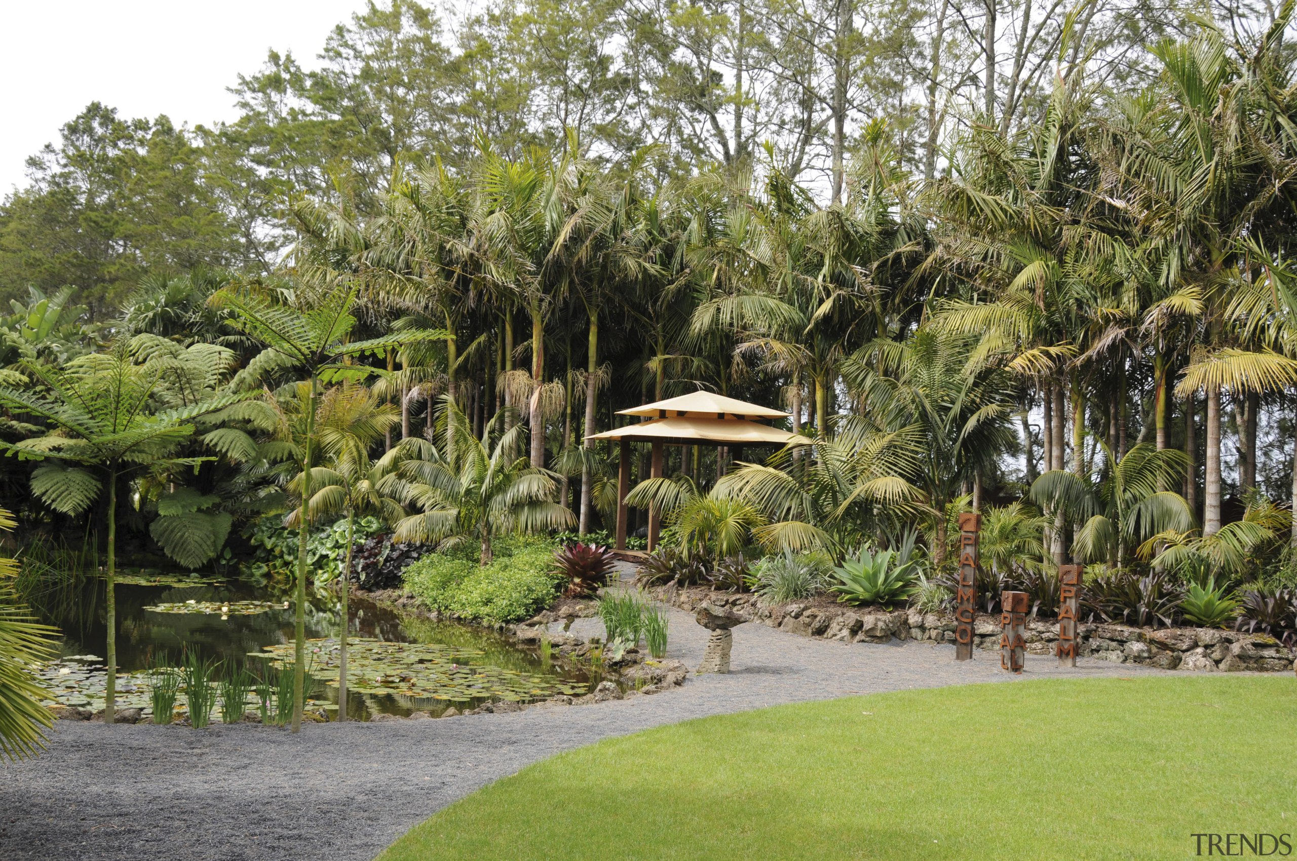 View of a designed and landscaped garden which arecales, backyard, botanical garden, estate, garden, grass, landscape, landscaping, lawn, outdoor structure, palm tree, plant, property, real estate, resort, tree, vegetation, yard, brown