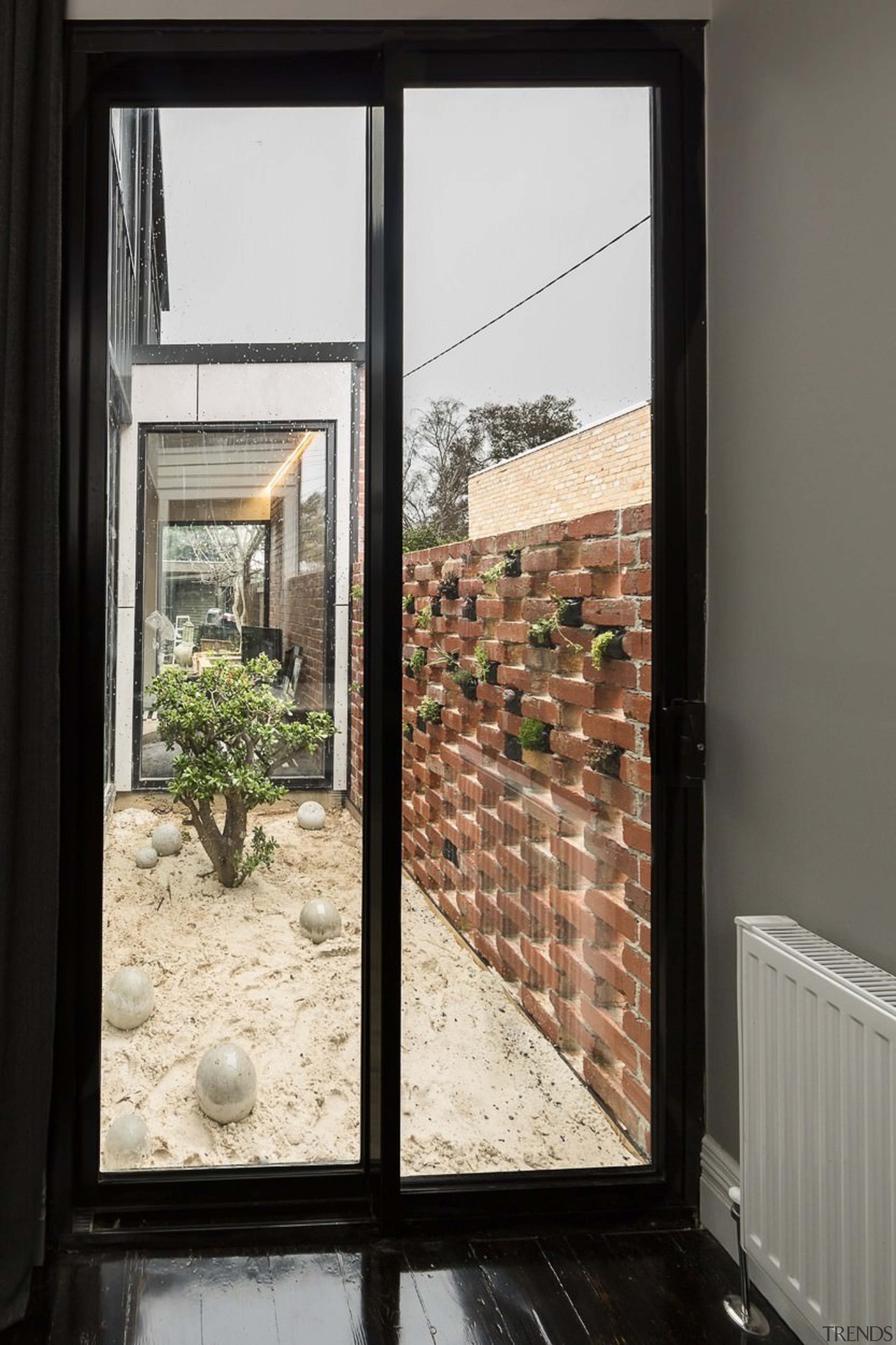 A contained garden provides a nice outlook for architecture, door, glass, home, house, interior design, window, black, white