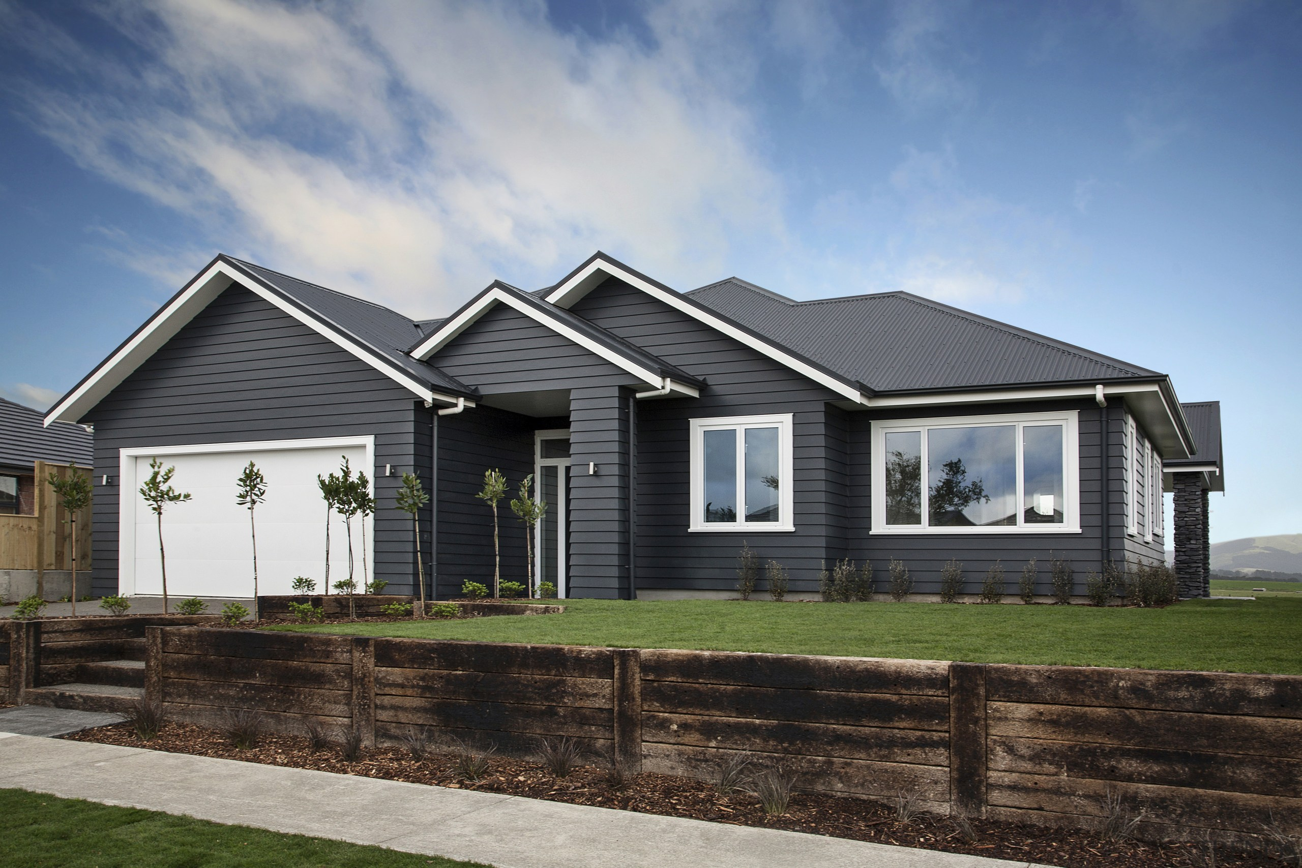 Landmark Homes new showhome, the Rata, is as building, cottage, elevation, estate, facade, farmhouse, home, house, landscape, property, real estate, residential area, siding, sky, suburb, gray, black