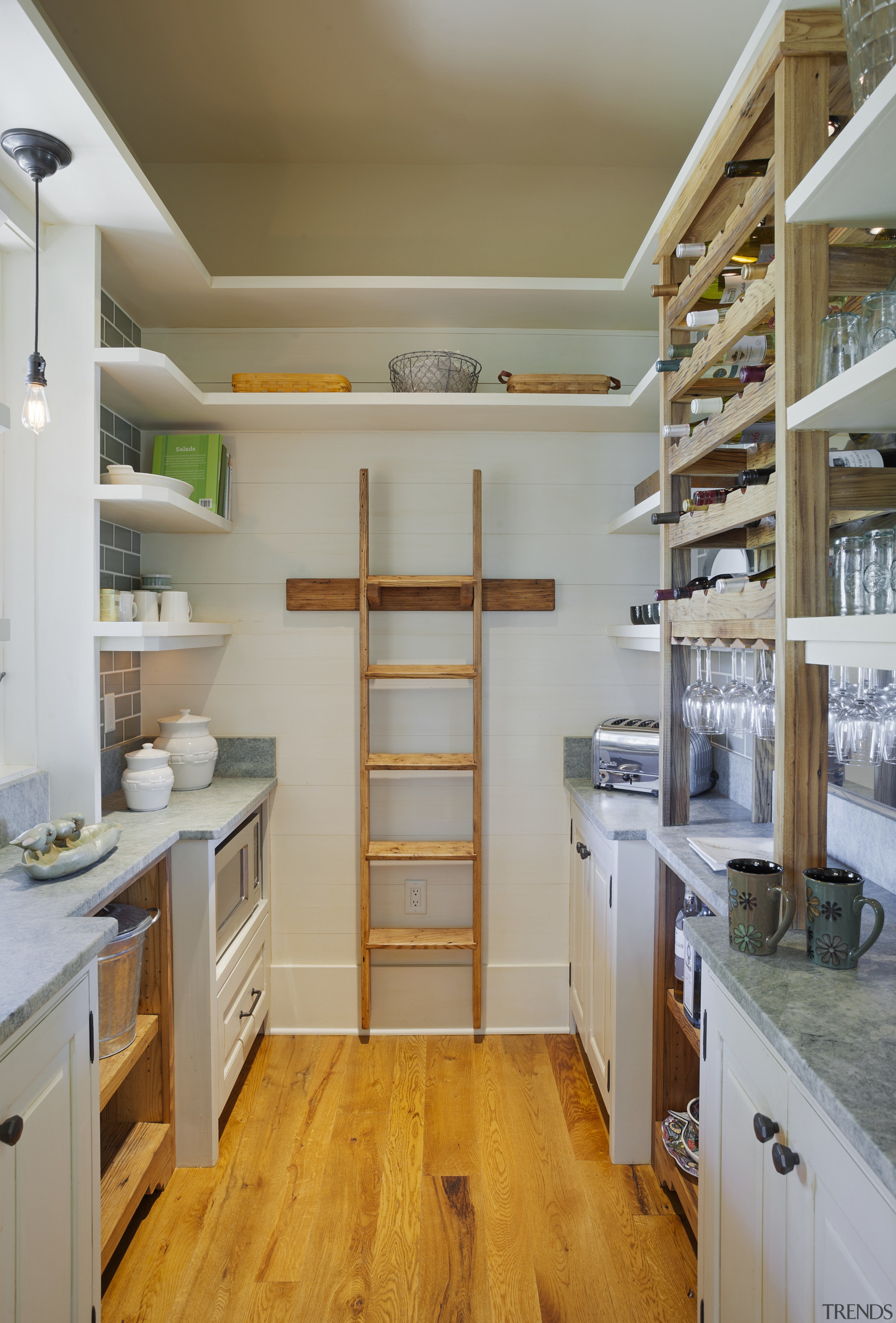 This scullery has a mirrored backsplash behind the cabinetry, countertop, cuisine classique, floor, flooring, hardwood, home, interior design, kitchen, laminate flooring, room, shelf, shelving, wood, wood flooring, gray, brown