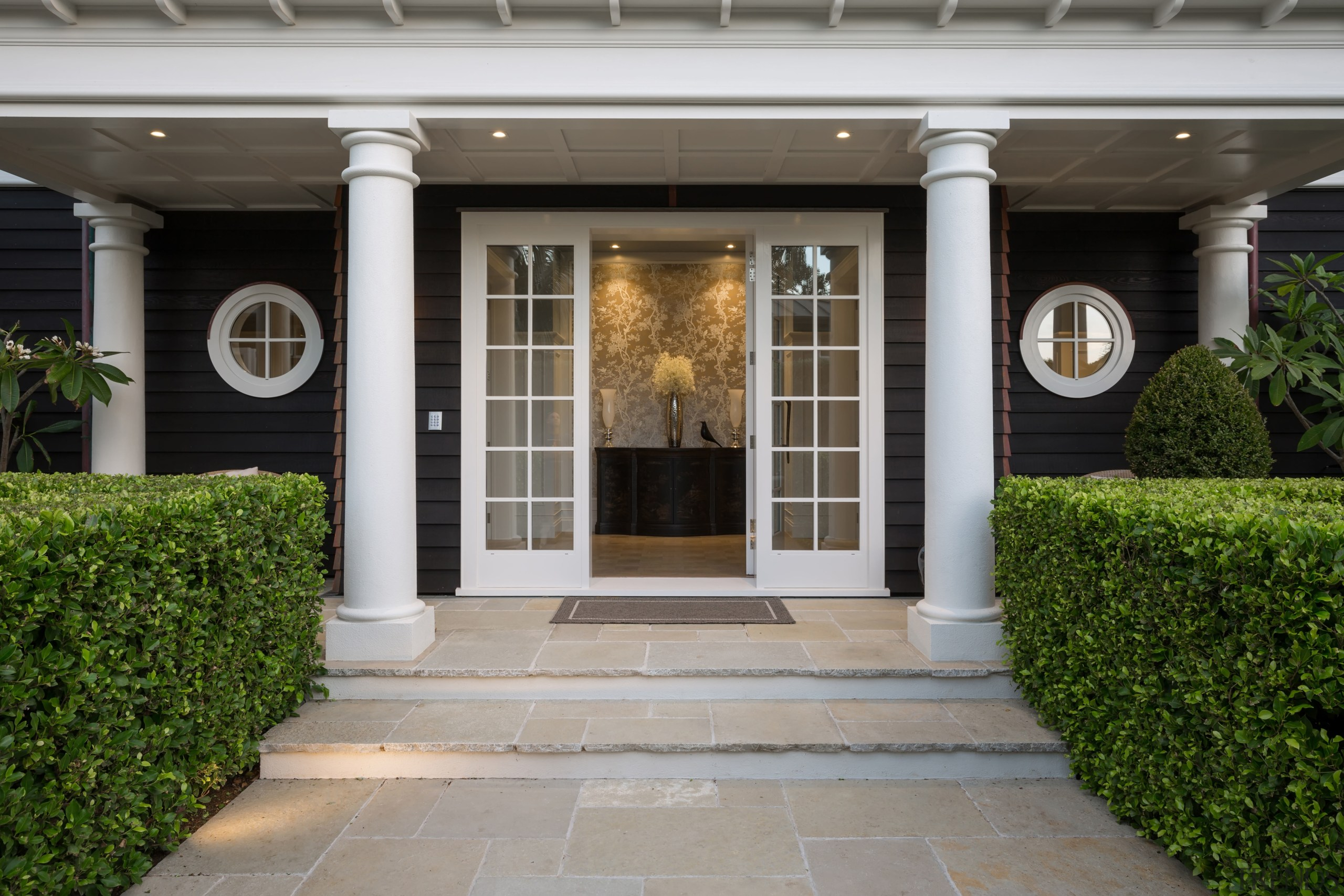 Classic columns and circular windows flank the front courtyard, door, estate, facade, home, house, outdoor structure, porch, property, real estate, structure, walkway, window, gray
