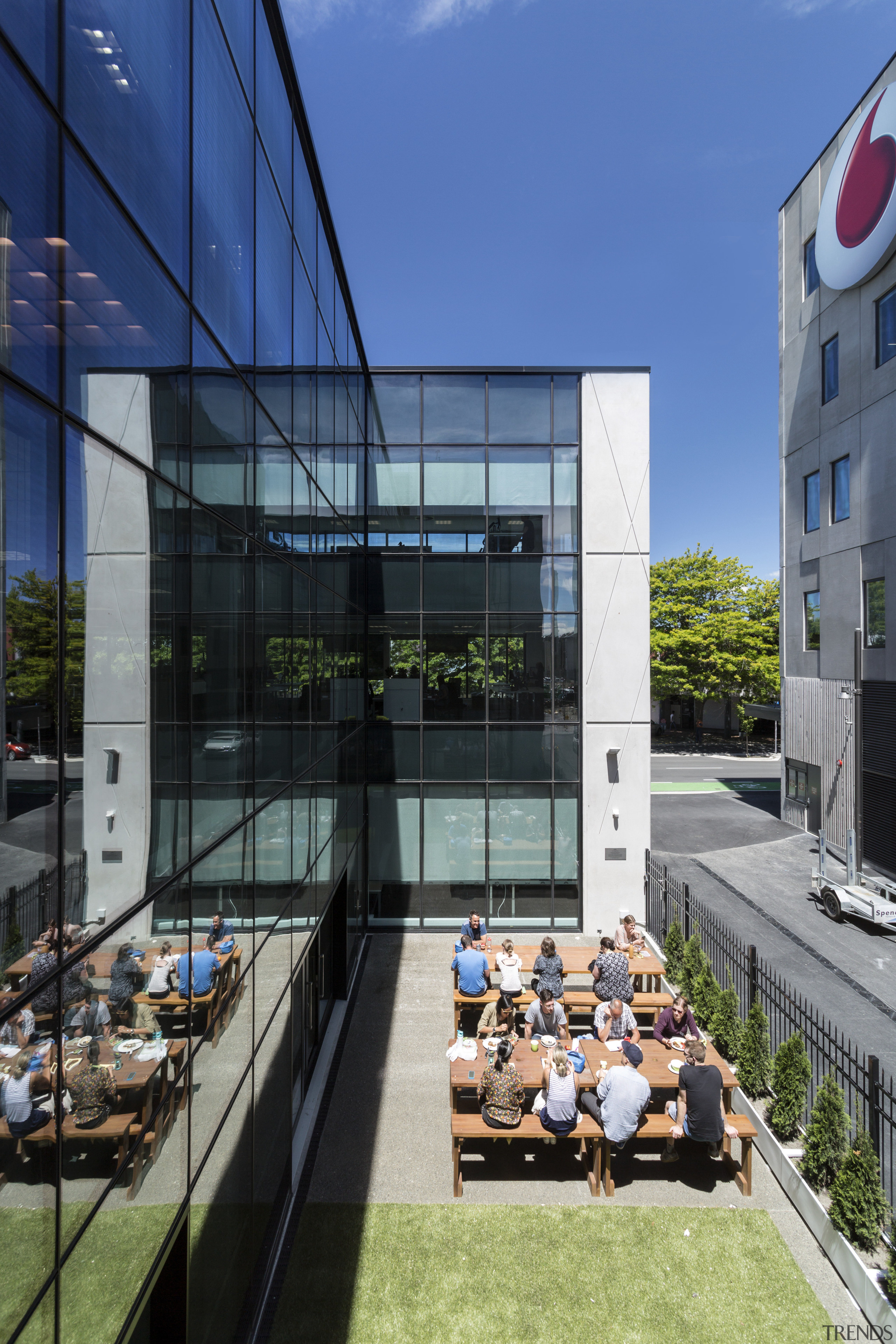 This side courtyard extends the staff cafeteria at apartment, architecture, building, condominium, corporate headquarters, daytime, facade, headquarters, house, mixed use, real estate, window, blue, black