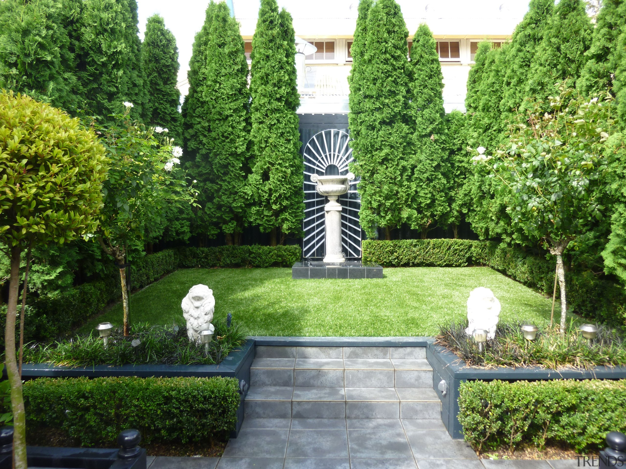 By creating two separate zones, this garden feels botanical garden, courtyard, estate, evergreen, garden, grass, hedge, landscape, landscaping, lawn, plant, shrub, tree, walkway, yard, green