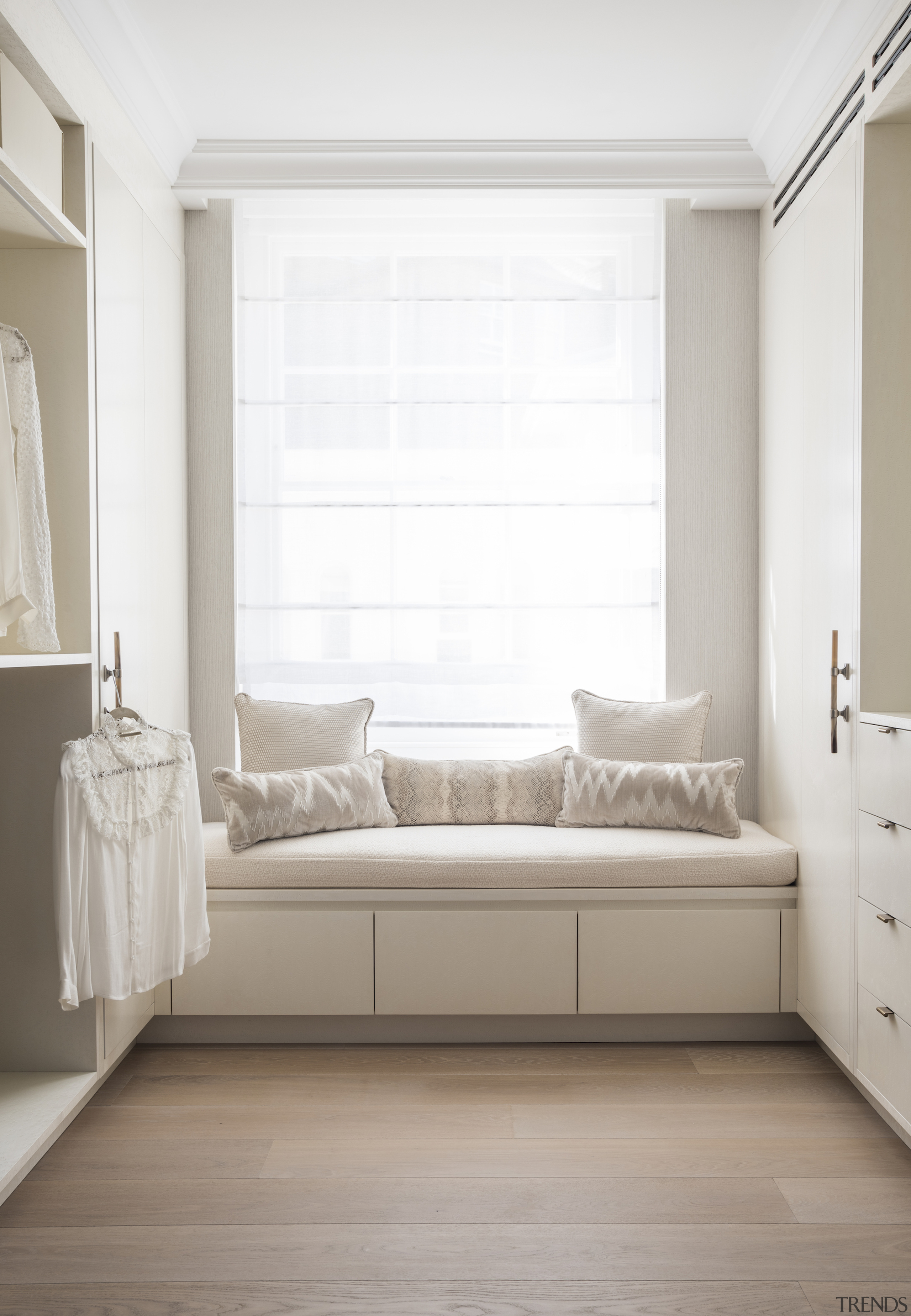 The walk-in wardrobe features an upholstered window seat
