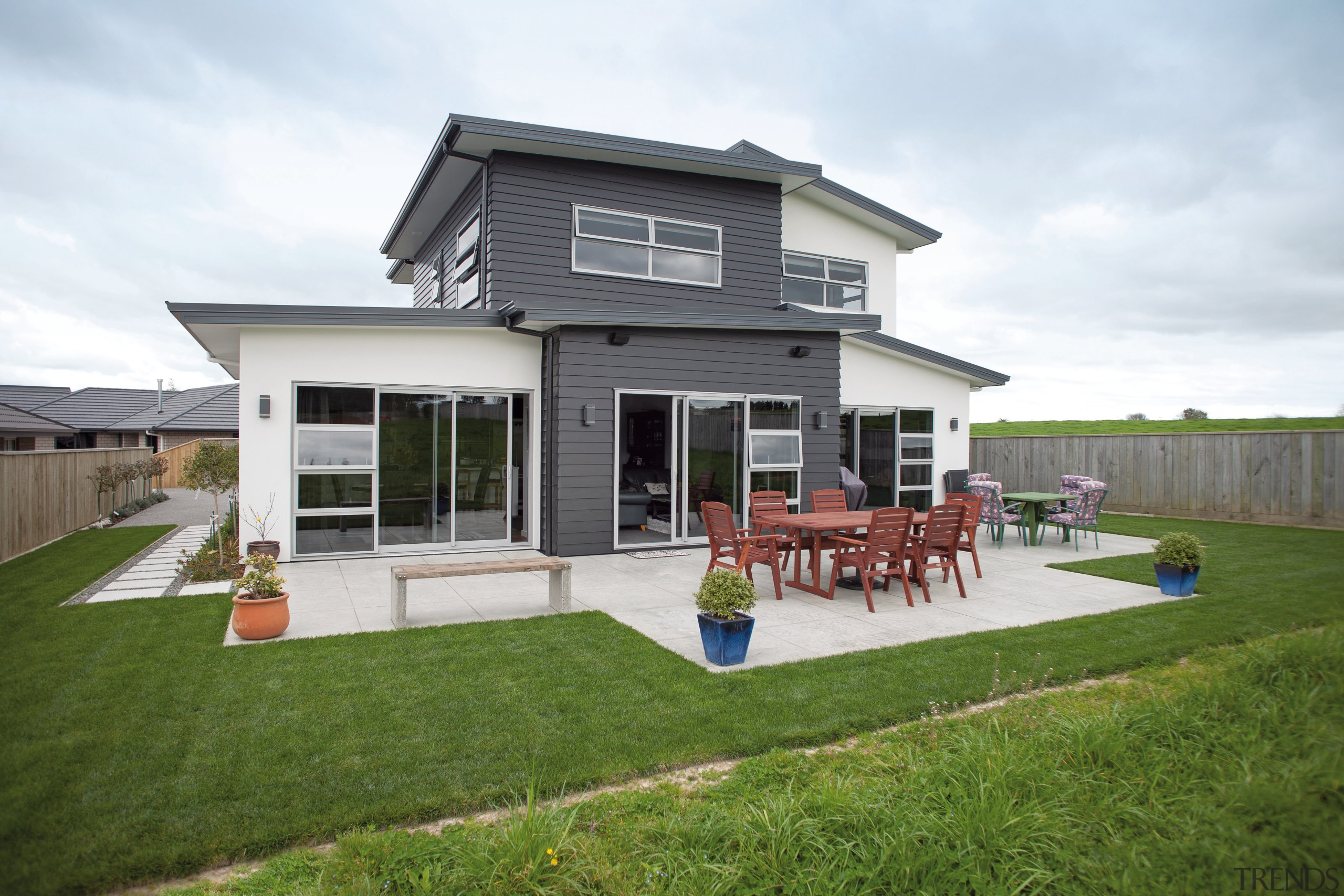 This new four-bedroom home, custom designed and built backyard, cottage, elevation, facade, home, house, property, real estate, residential area, yard, white, brown