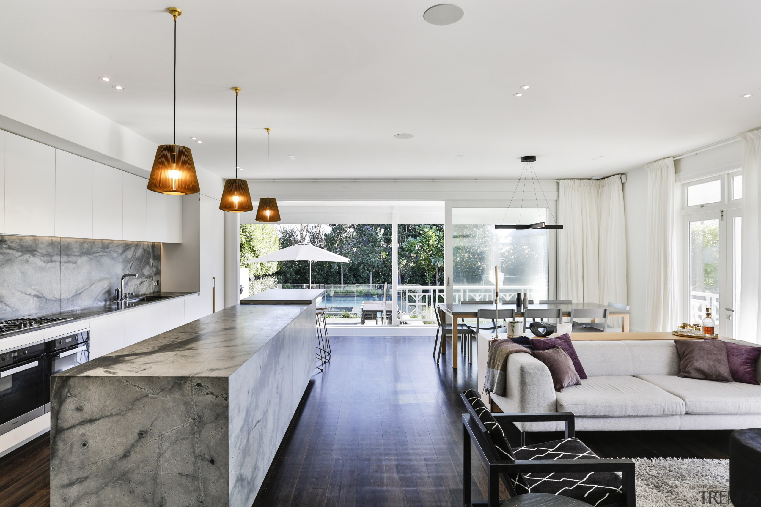 The stone-clad island, perimeter benchtop and splashback have house, interior design, living room, villa, timber floor, stone island, kitchen, Matt Brew Architect