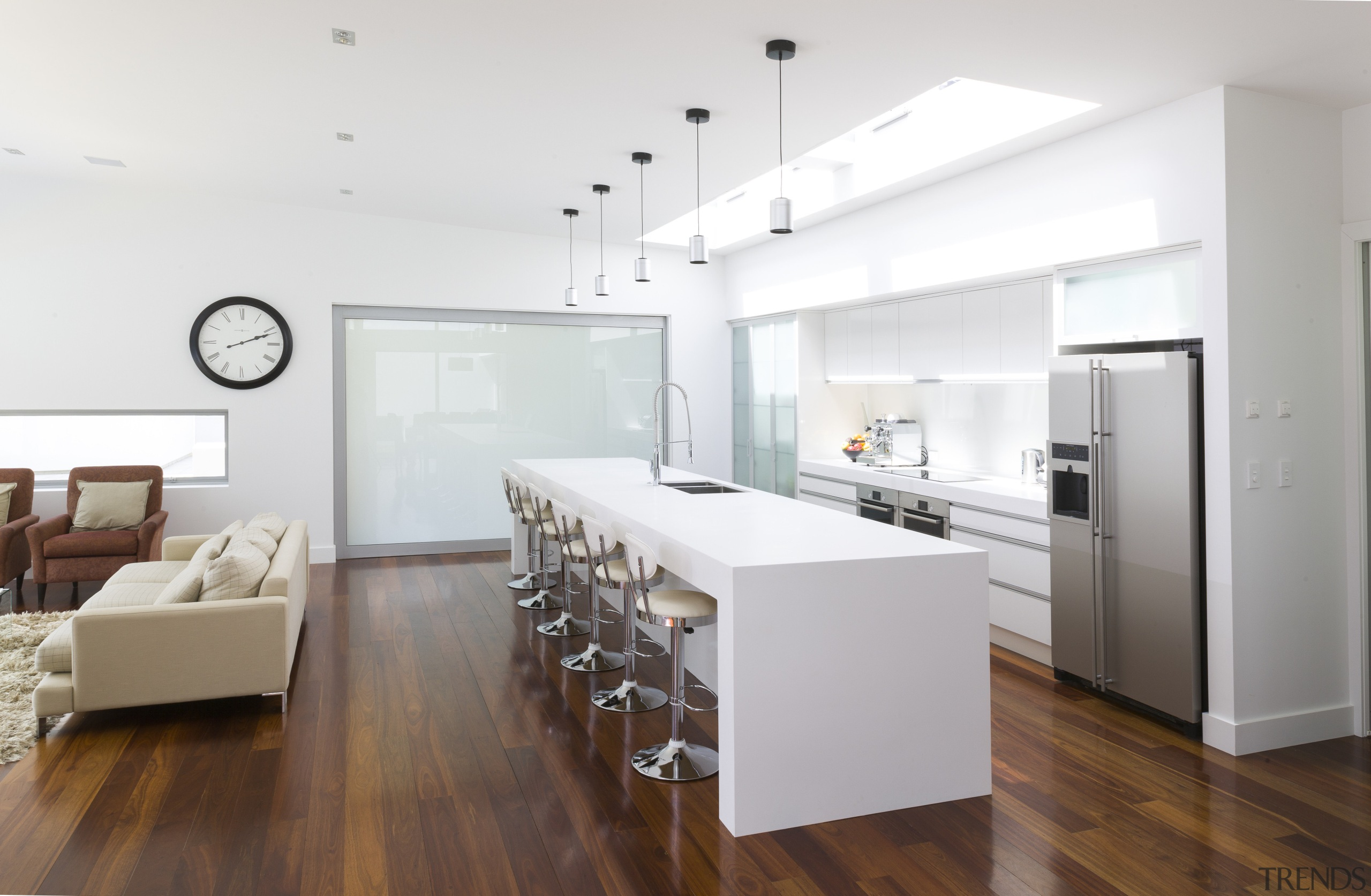 Contemporary white kitchen with large island. Internal sliding floor, flooring, interior design, interior designer, kitchen, living room, real estate, wood flooring, white