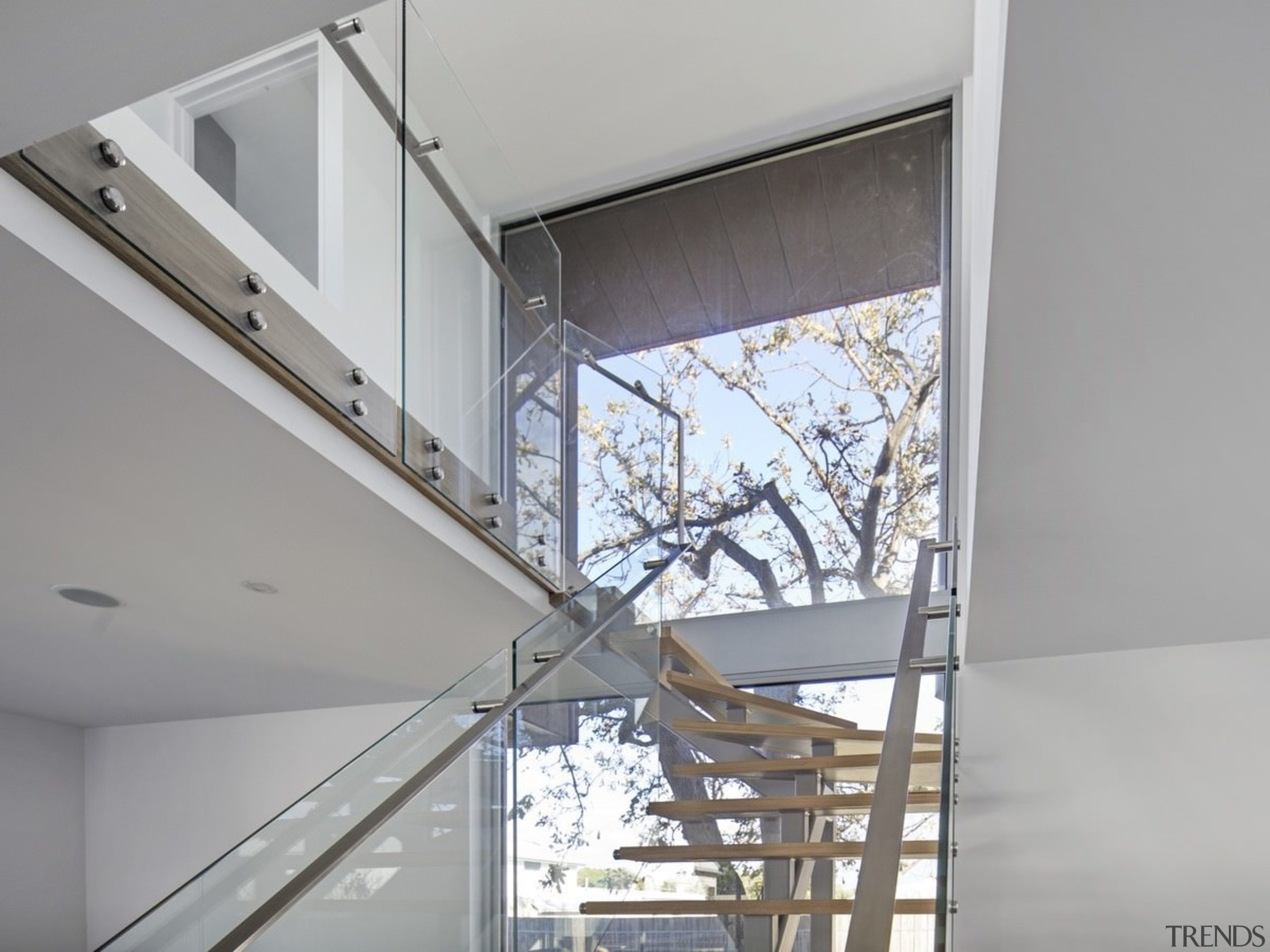This floating stairway rises up to the second architecture, ceiling, daylighting, glass, handrail, house, interior design, stairs, structure, window, gray