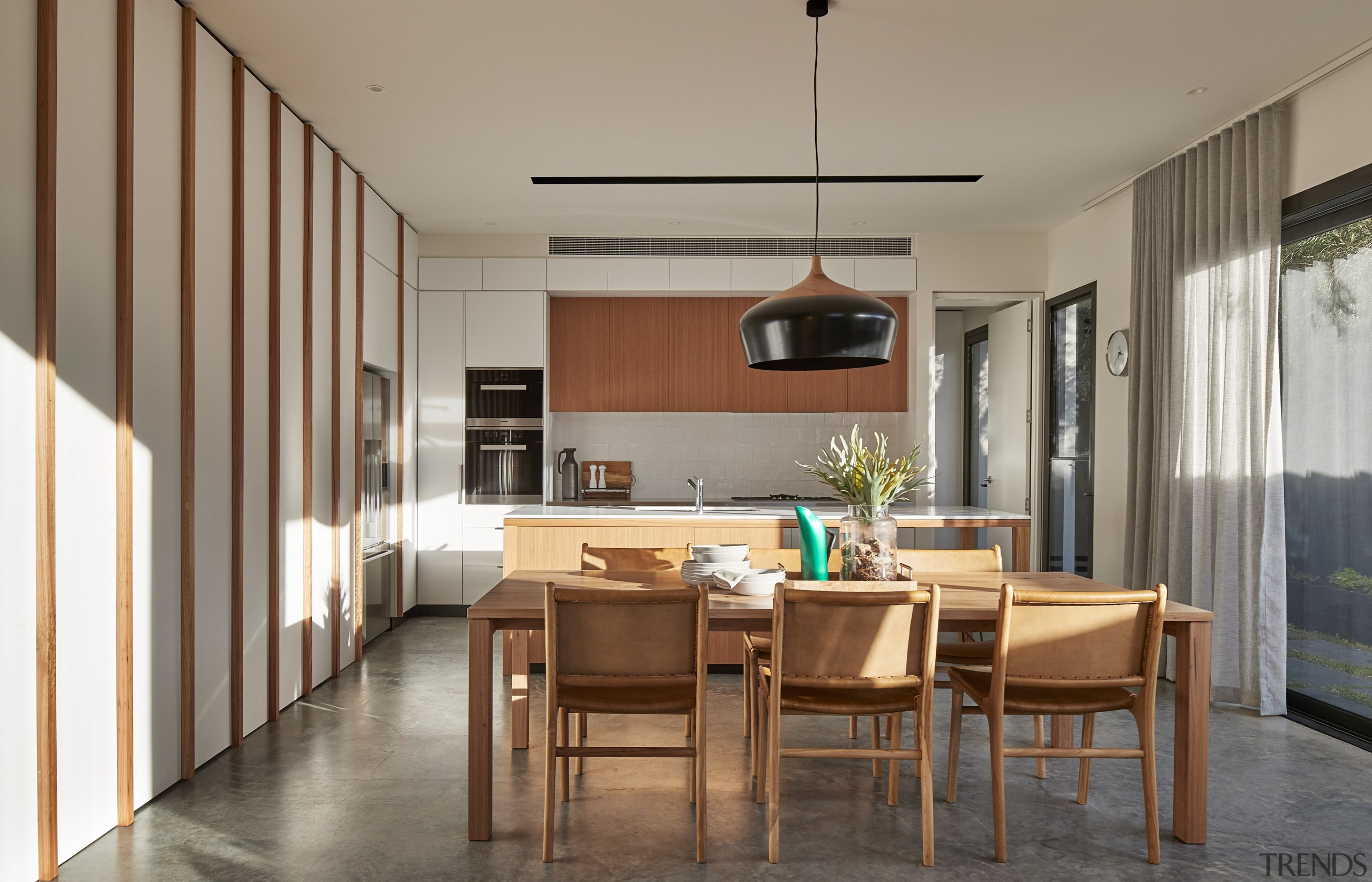The kitchen and dining area in the contemporary architecture, building, cabinetry, ceiling, countertop, cupboard, dining room, door, floor, flooring, furniture, hardwood, home, house, interior design, kitchen, light fixture, lighting, living room, material property, property, real estate, room, table, wall, wood, wood flooring, gray