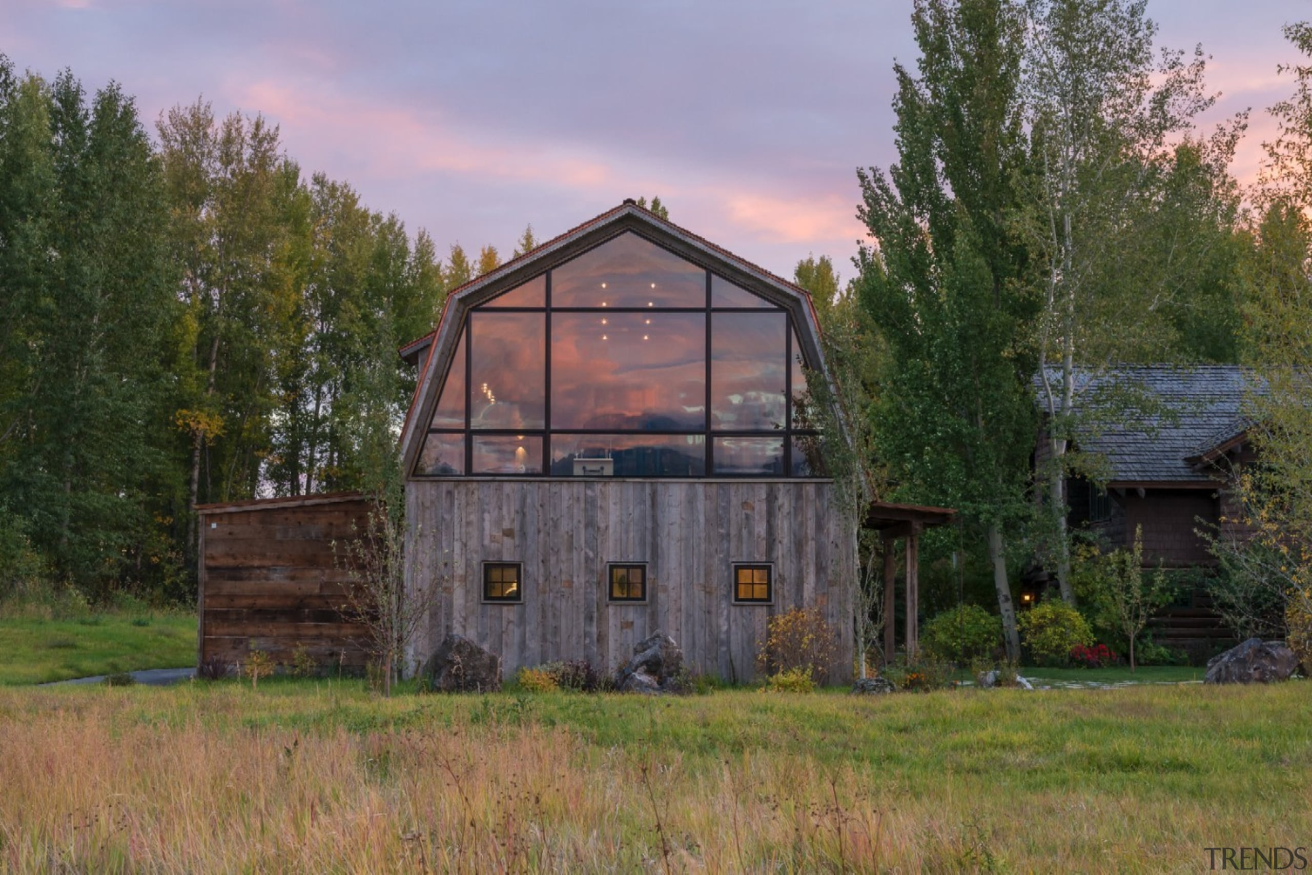 This large window looks out to the distant barn, cottage, farm, farmhouse, grass, home, house, hut, land lot, landscape, property, real estate, rural area, shack, shed, tree, brown
