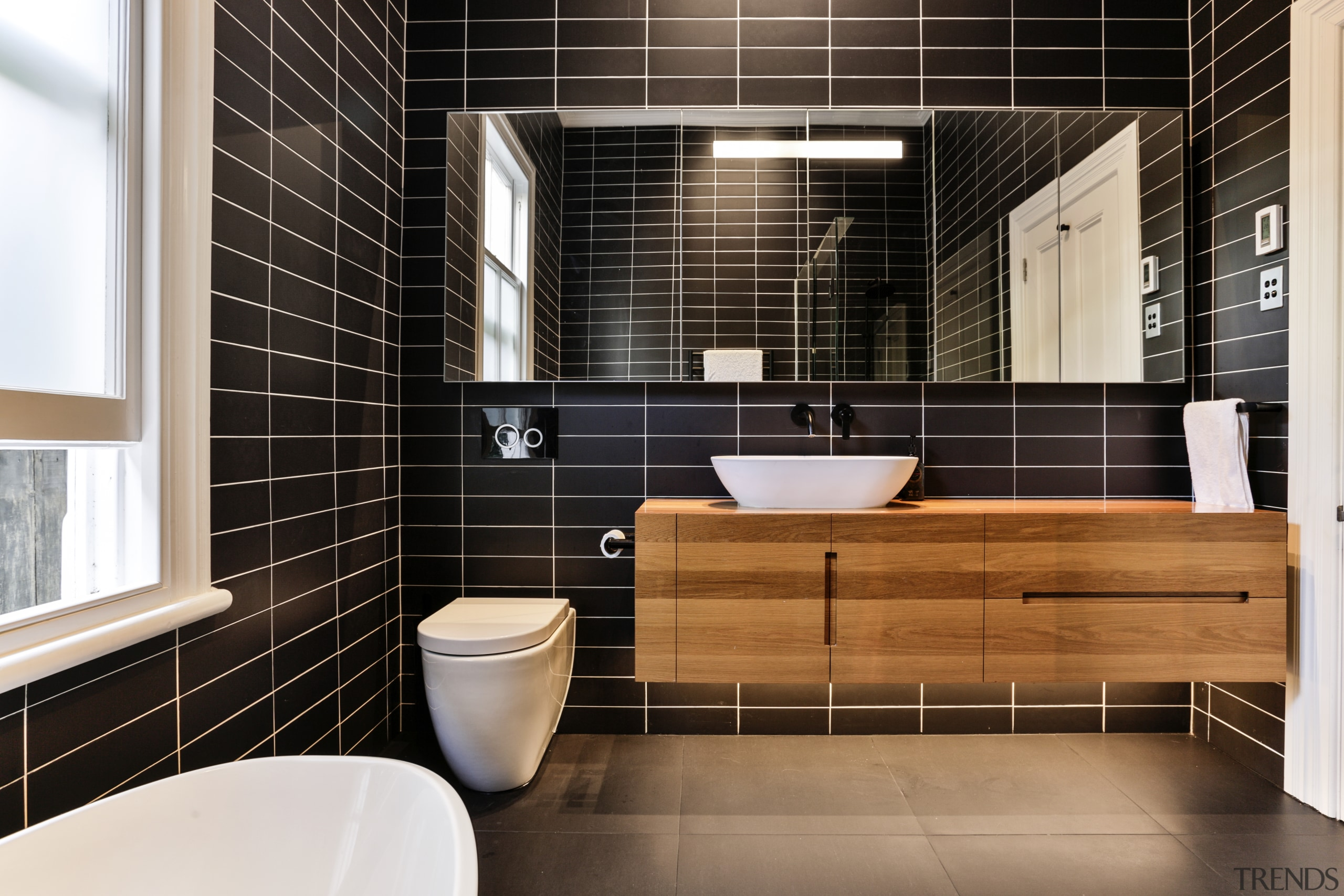 ​​​​​​​While classic elements were retained elsewhere, the bathrooms bathroom, floor, flooring, home, interior design, room, tile, black, timber vanity, basin
