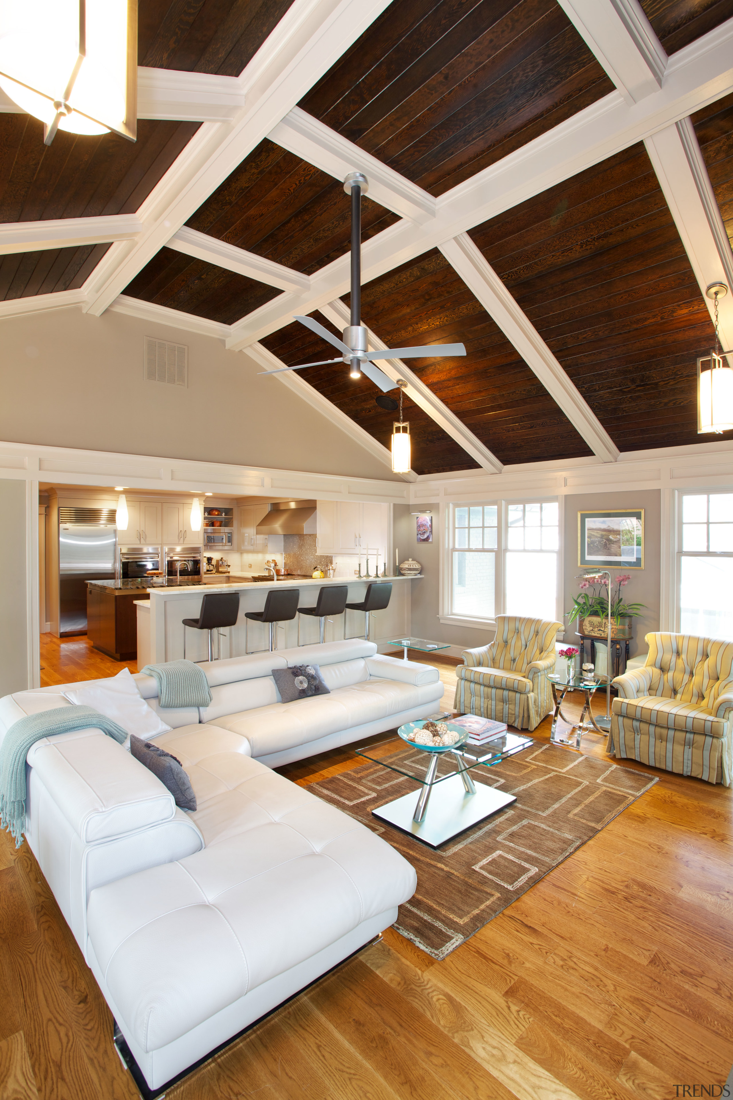 This open-plan family room and kitchen are part beam, ceiling, daylighting, floor, flooring, hardwood, home, interior design, living room, loft, real estate, room, wood, wood flooring, white, brown