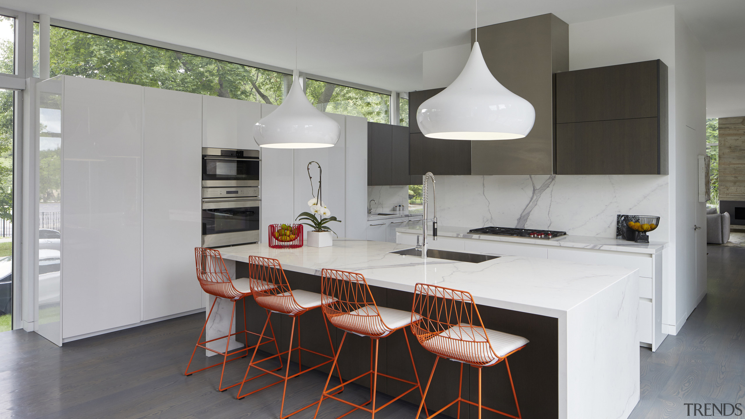 The predominantly white kitchen picks up on the architecture, bar stool, building, cabinetry, ceiling, countertop, dining room, floor, flooring, furniture, home, house, interior design, kitchen, kitchen stove, loft, material property, property, real estate, room, stool, table, tile, gray