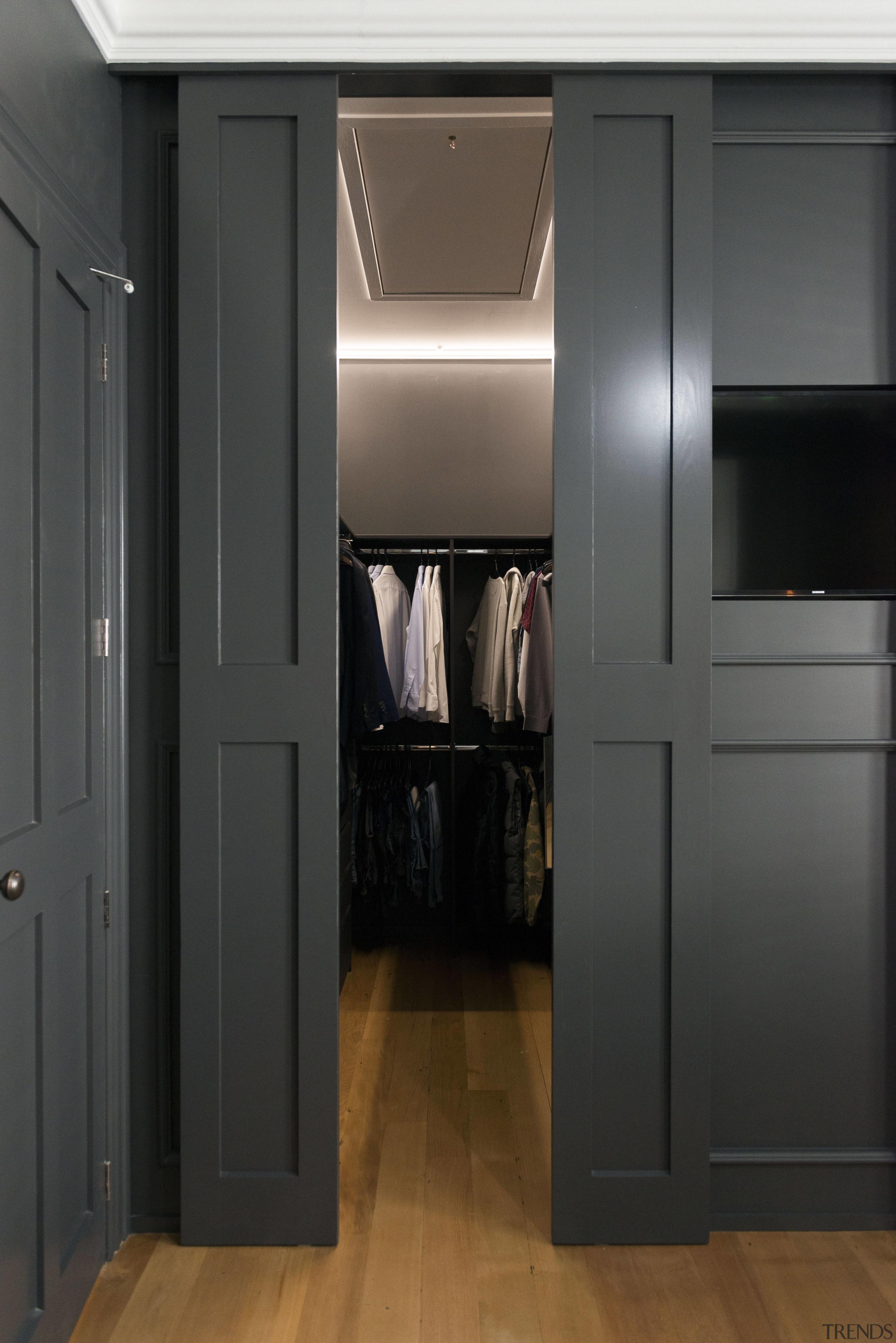 Open sesame  dark grey wall panelling disguises cabinetry, closet, door, floor, interior design, room, black
