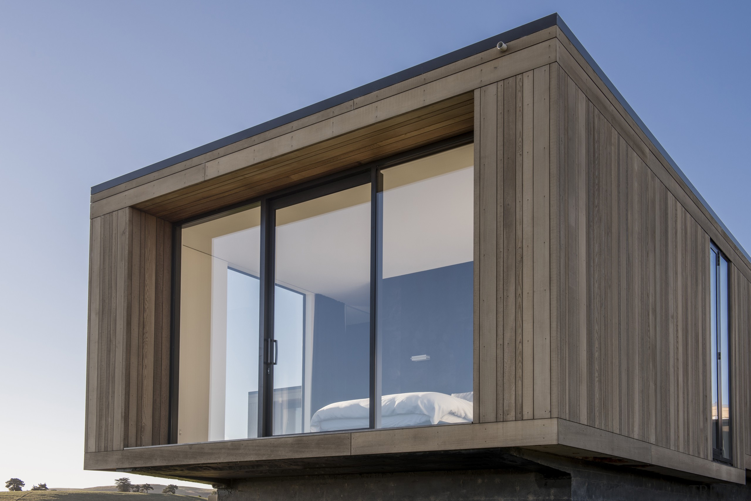 The central bedroom wing extends beyond the flanking architecture, building, facade, home, house, siding, window, gray