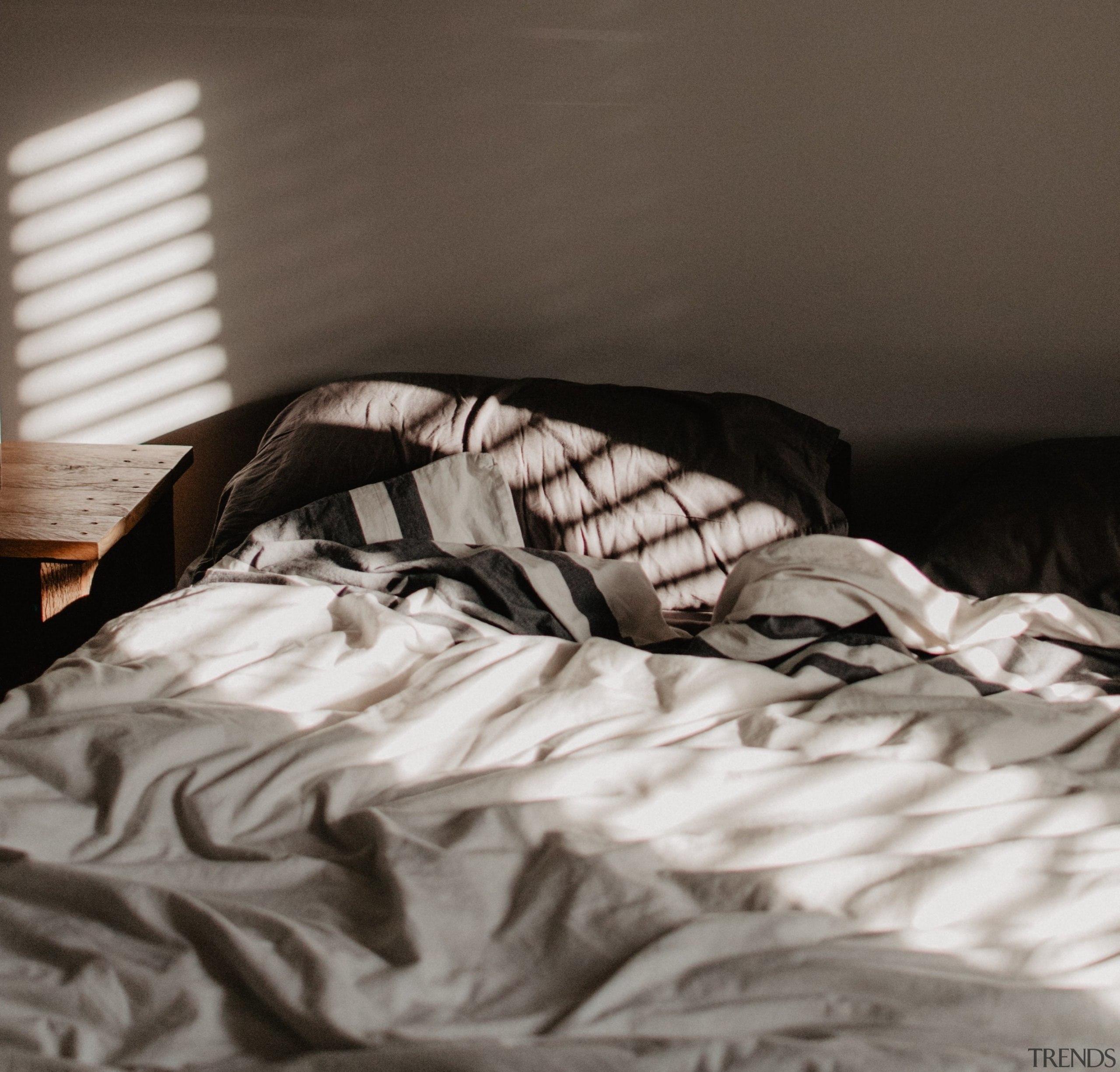 Unmade bed bedroom sunlight -