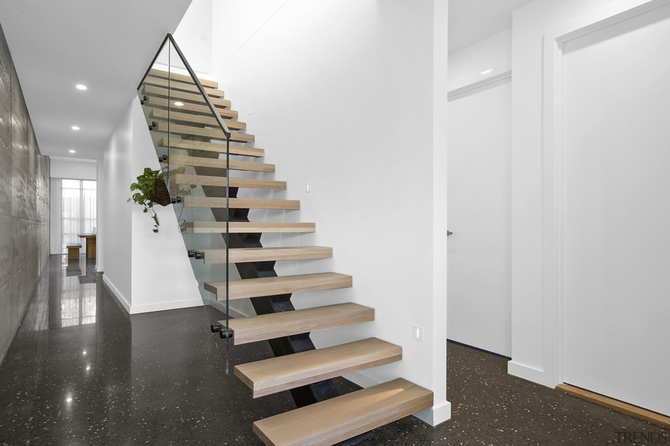 A floating stair with glass balustrade runs up architecture, daylighting, floor, flooring, handrail, interior design, product design, stairs, white