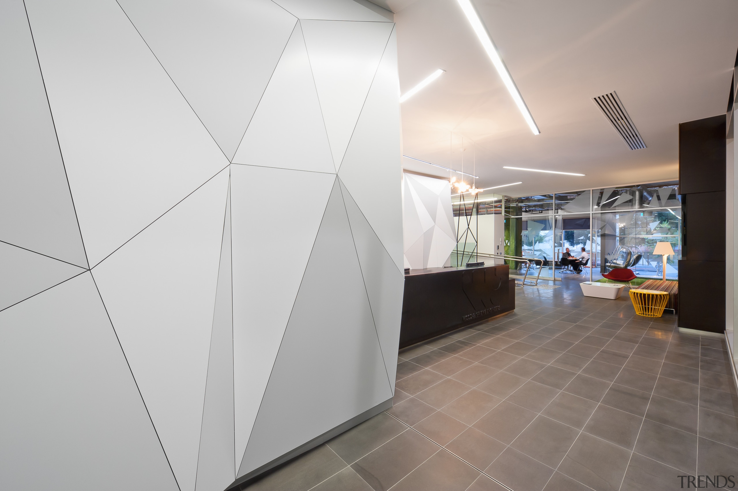 A multifaceted facade behind the reception desk of architecture, ceiling, daylighting, floor, interior design, product design, gray
