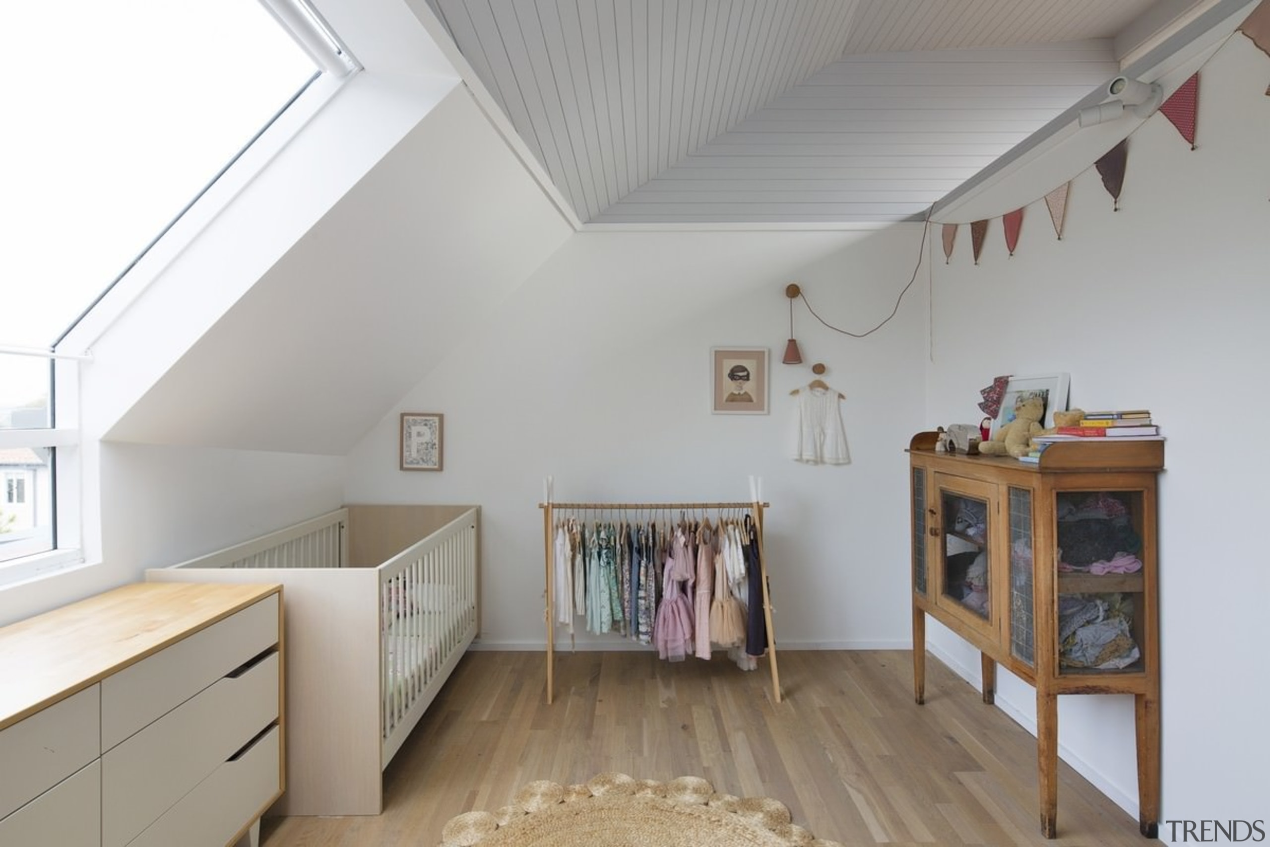 An angled window allows for maximum sunlight, while attic, ceiling, daylighting, floor, home, house, interior design, loft, property, real estate, room, wood, gray, white